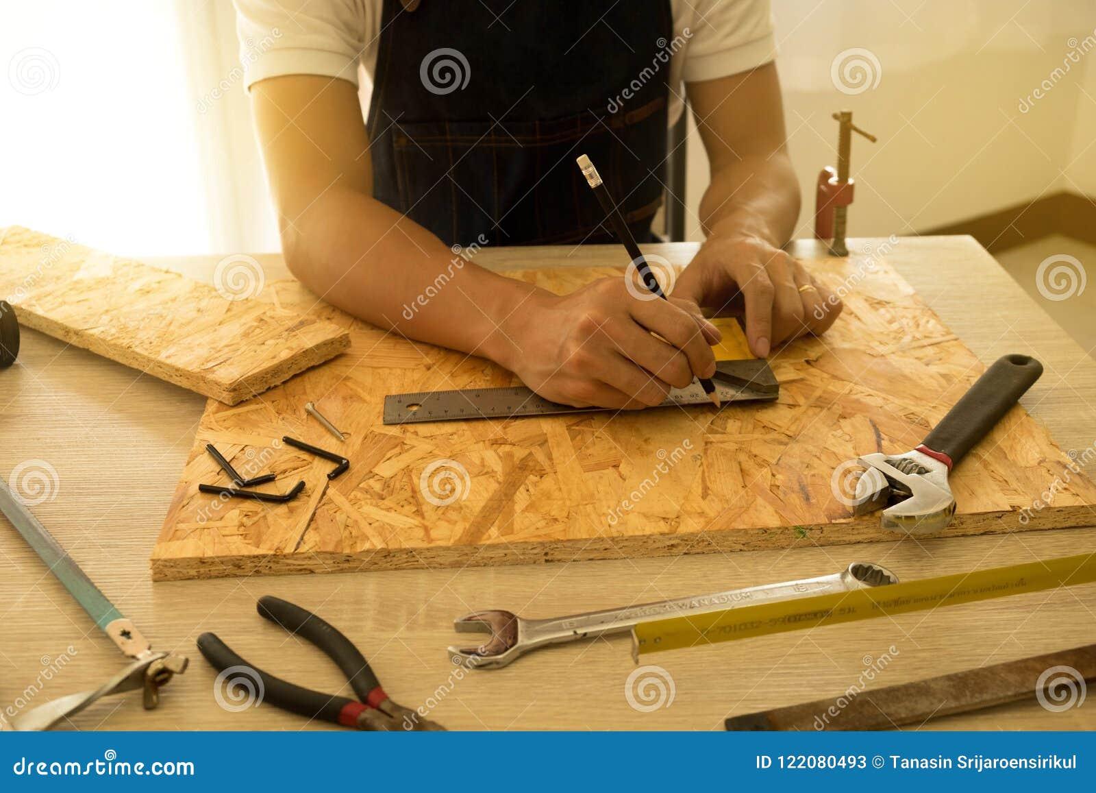 Zakończenie męski cieśla wręcza rysunek ocenę na drewnianej podłoga