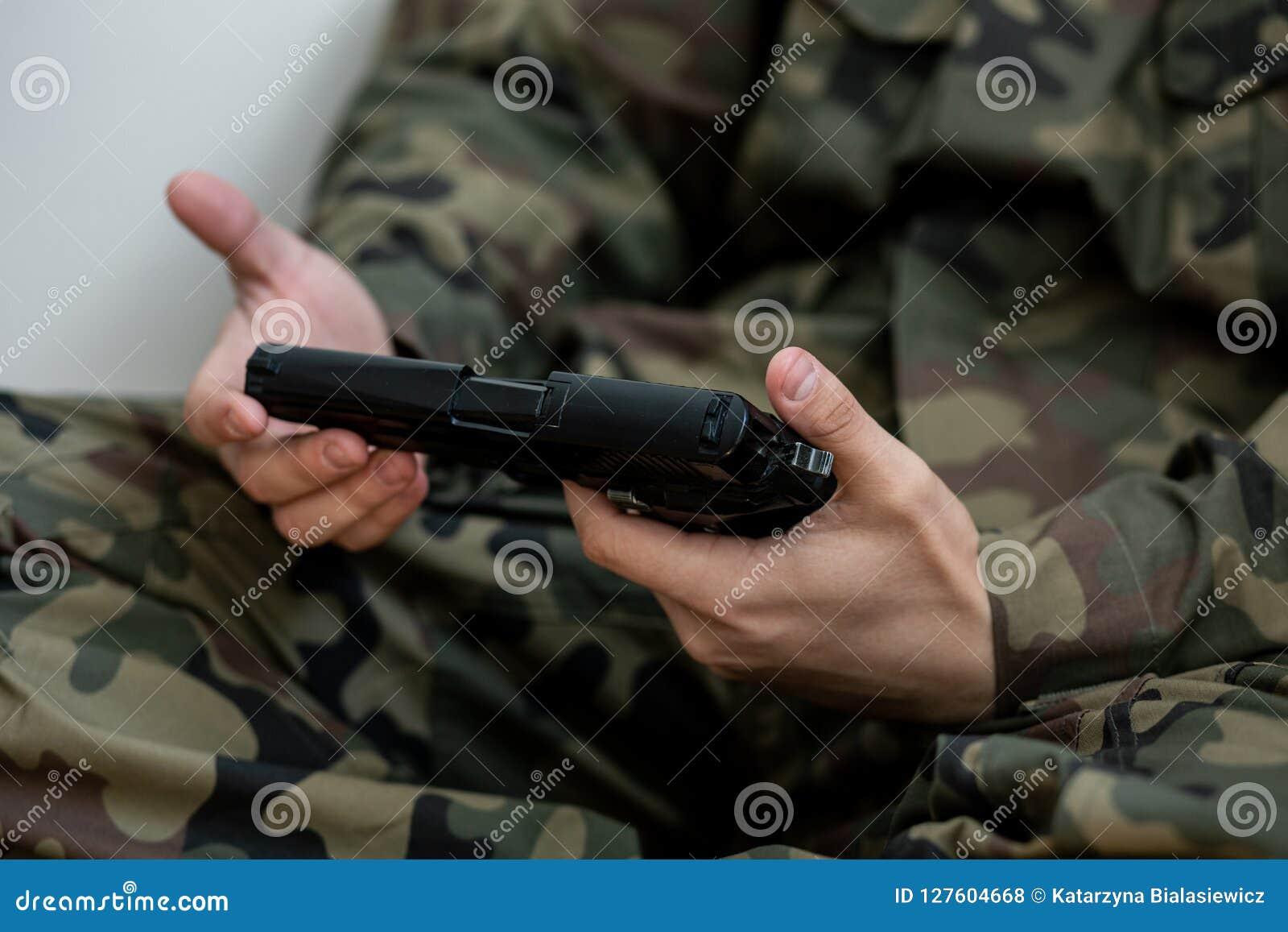 Zakończenie na żołnierzu w zielonym Moro mundurze z pistoletem w rękach