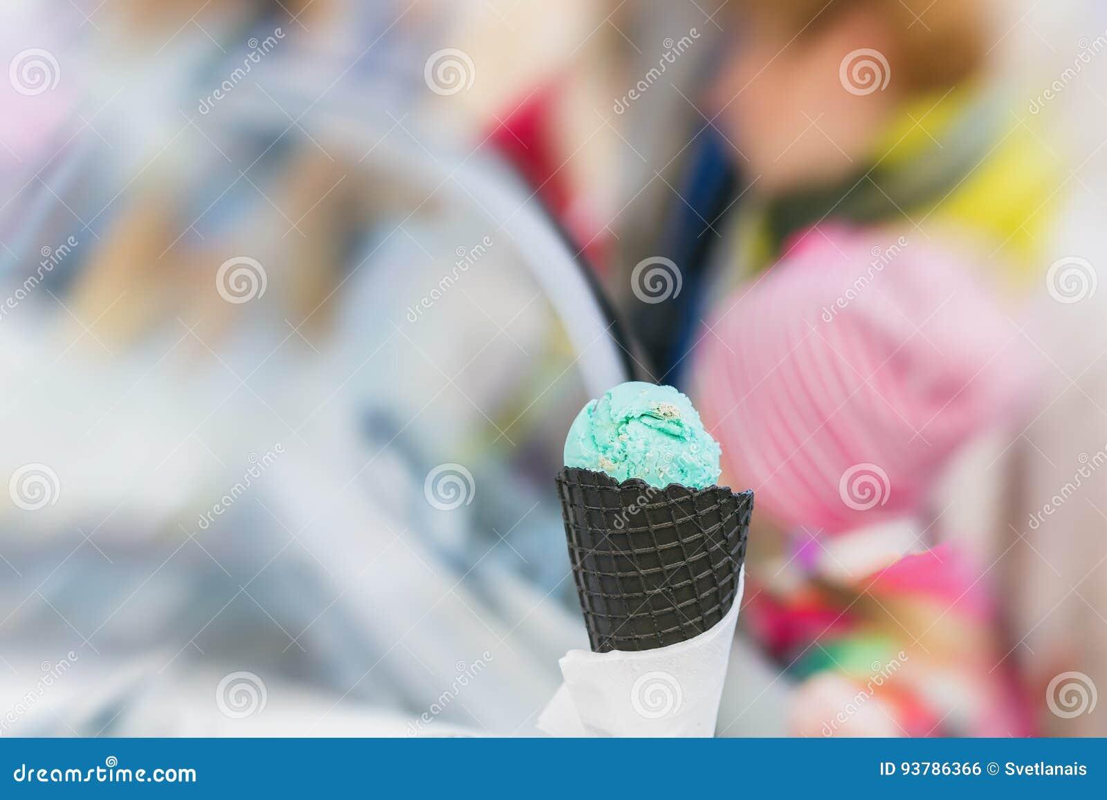 Zakończenie owocowego lody zielony kolor w Czarnym gofra rożku, tło z słodkim deserem Istna scena w sklepie