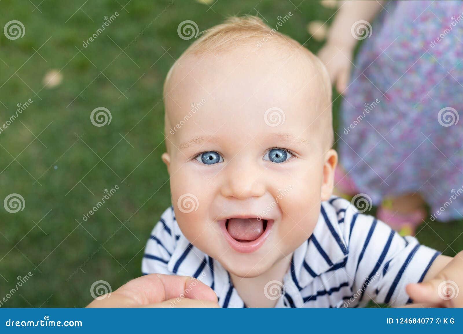 Zakończenie portret śliczna caucasian chłopiec uśmiecha się zabawę z rodzicami outdoors i ma Szczęśliwa dziecięca twarz z dużym