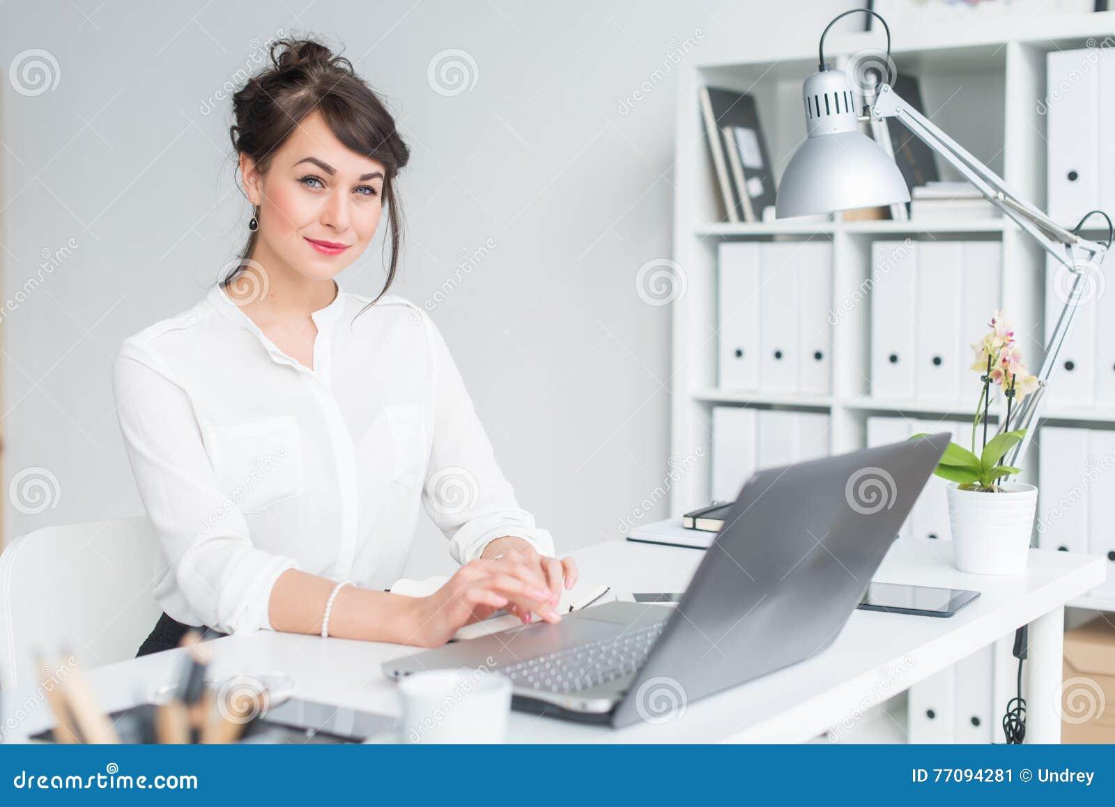 Zakończenie portret bizneswoman przy jej miejscem pracy pracuje z komputerem osobistym, patrzejący w kamerze, jest ubranym biurow