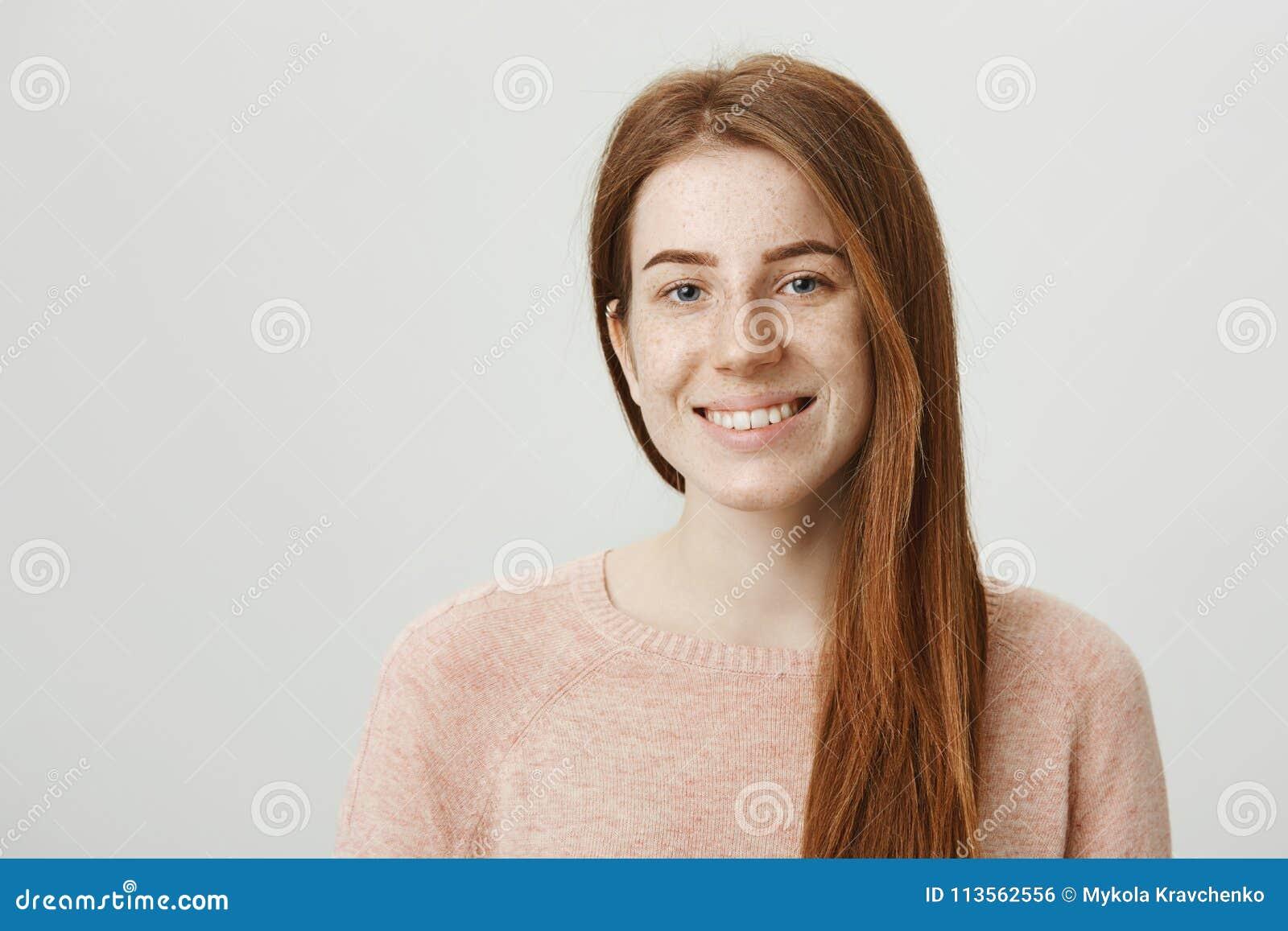 Zakończenie portret ciekawy i śliczny rudzielec kobiety model ono uśmiecha się szeroko podczas gdy patrzejący z miłym spojrzeniem