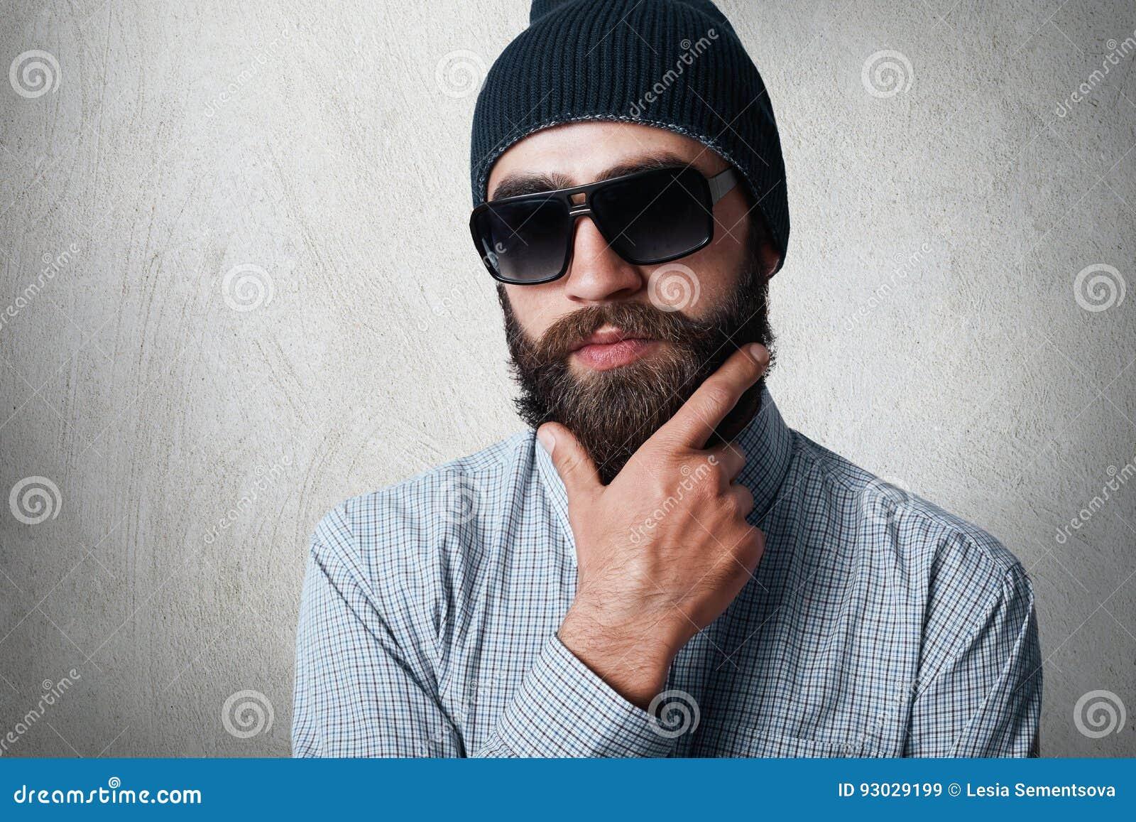 Zakończenie portret przystojny brodaty mężczyzna jest ubranym elegancką czarną nakrętkę, sprawdzać koszula i okulary przeciwsłone