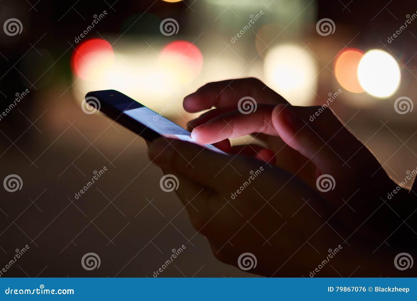 Zakończenie ręka używać telefon w nighttime na ulicie