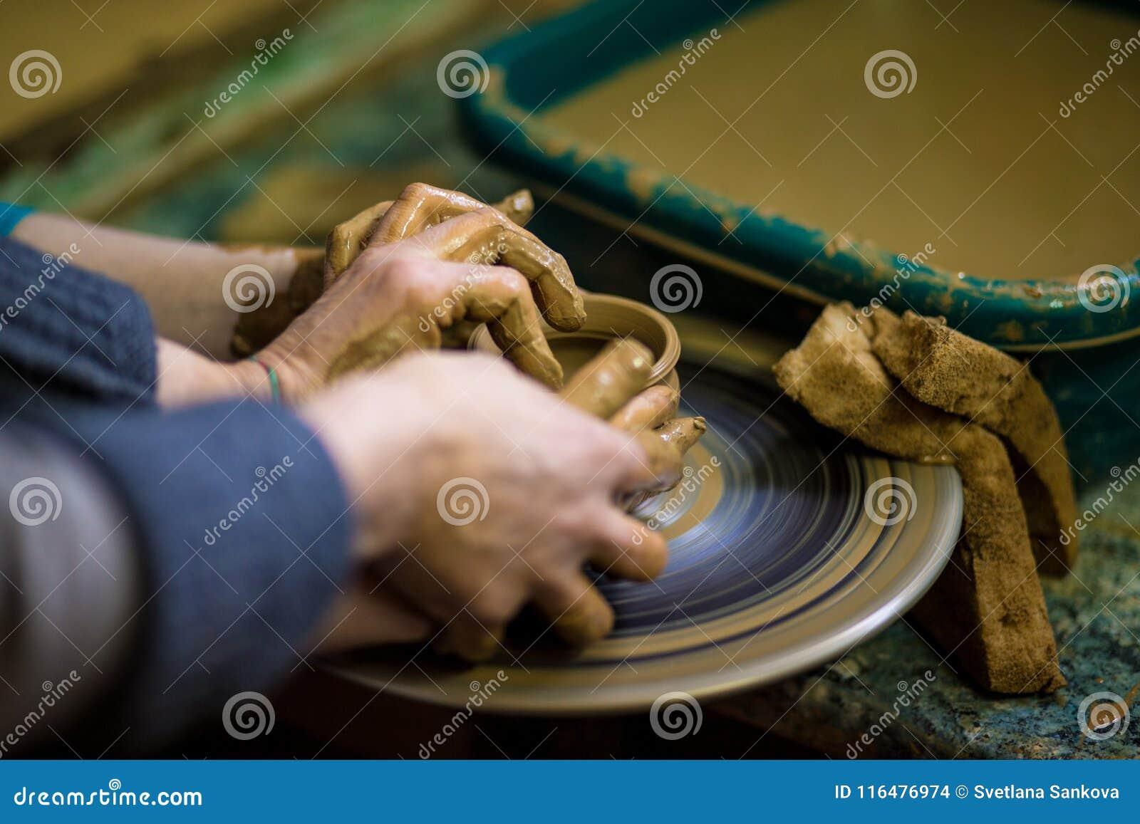 Zakończenie ręki garncarka w fartuchu robi wazie od gliny