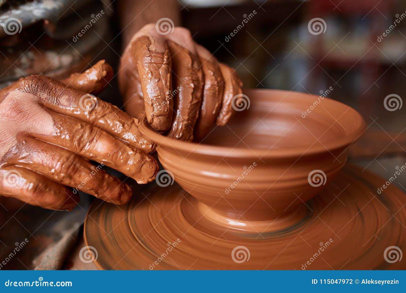 Zakończenie ręki męska garncarka w fartuchu robi wazie od gliny, selekcyjna ostrość