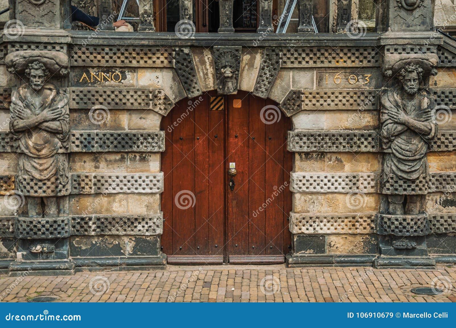 Zakończenie statuy wokoło lesistego drzwi przed gothic urzędu miasta budynkiem Gouda w chmurnym dniu