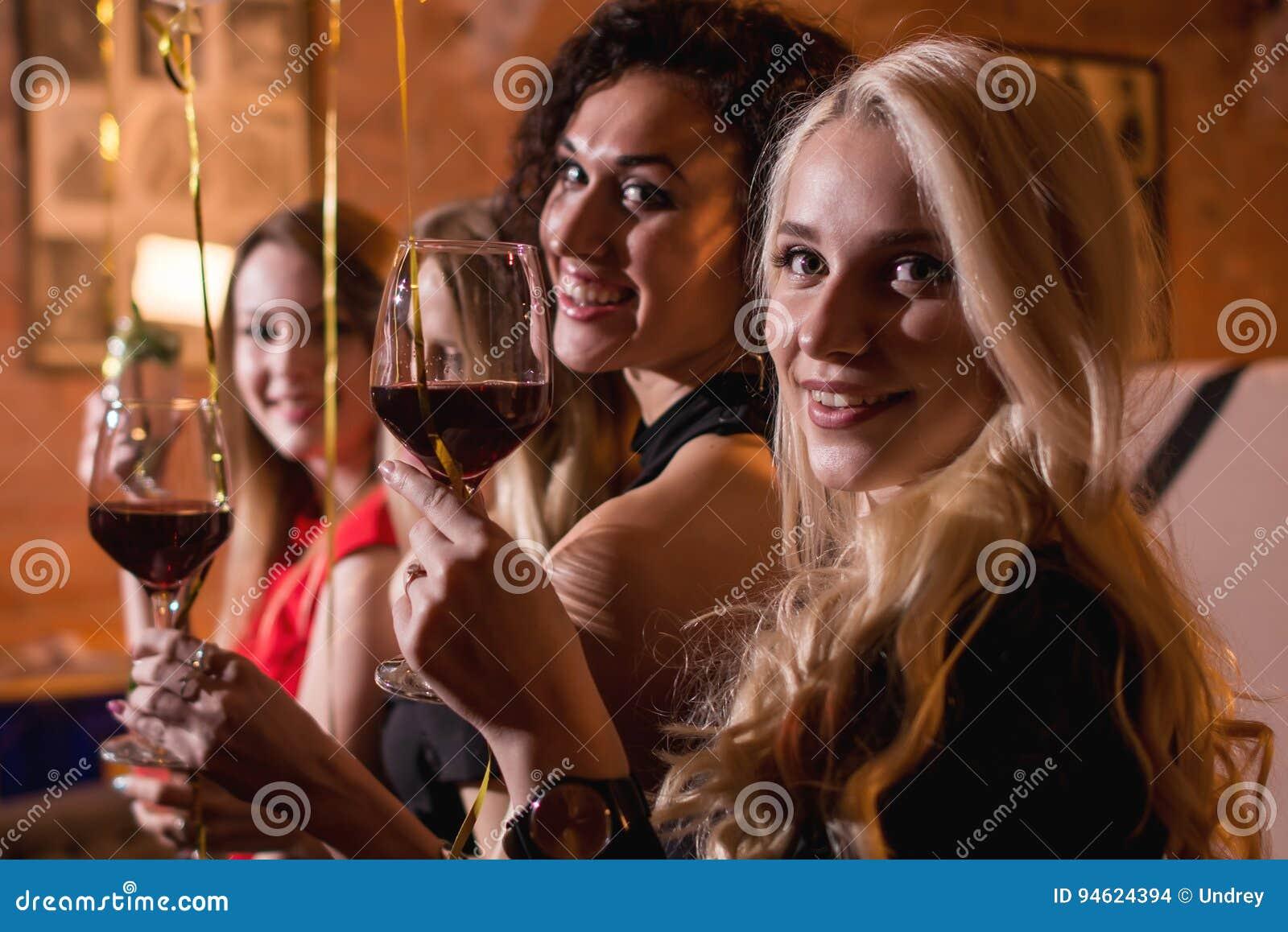 Zakończenie strzelał pozytywni piękni żeńscy przyjaciele podnosi szkła wino szczęśliwego wydarzenia obsiadanie w modnym