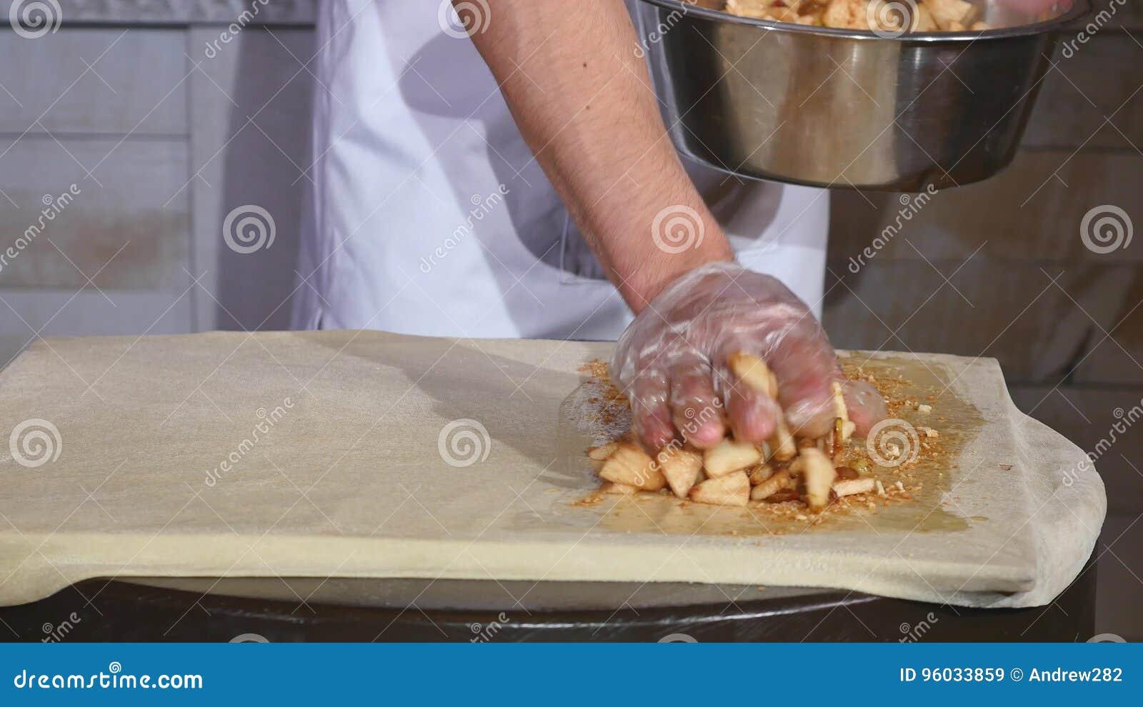 Zakończenie szef kuchni wręcza kładzenia jabłka kulebiak w restauracyjnej kuchni