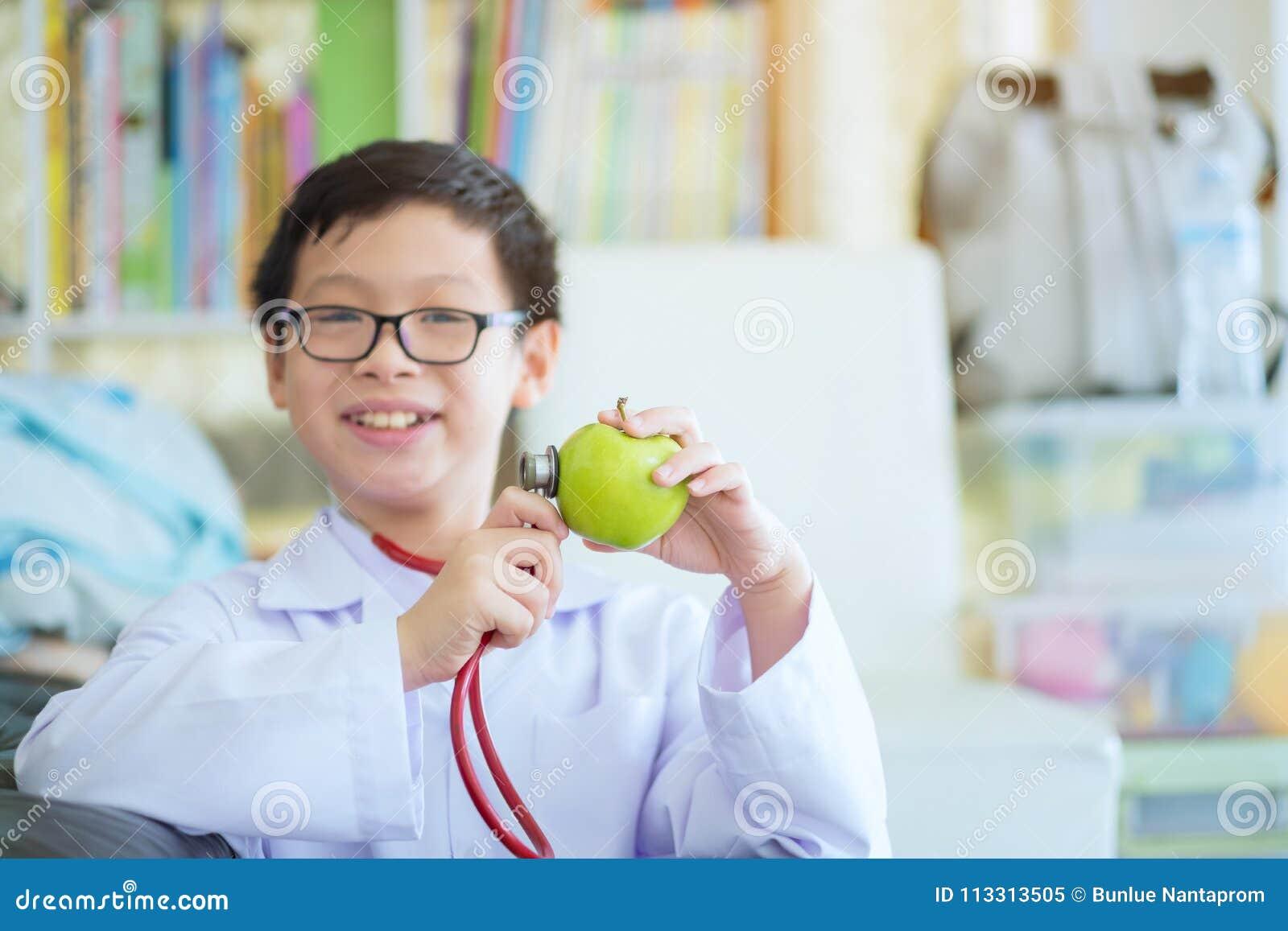 Zakończenie up chłopiec ręki z zielonym jabłkiem, Mały śliczny chłopiec przyszłości d