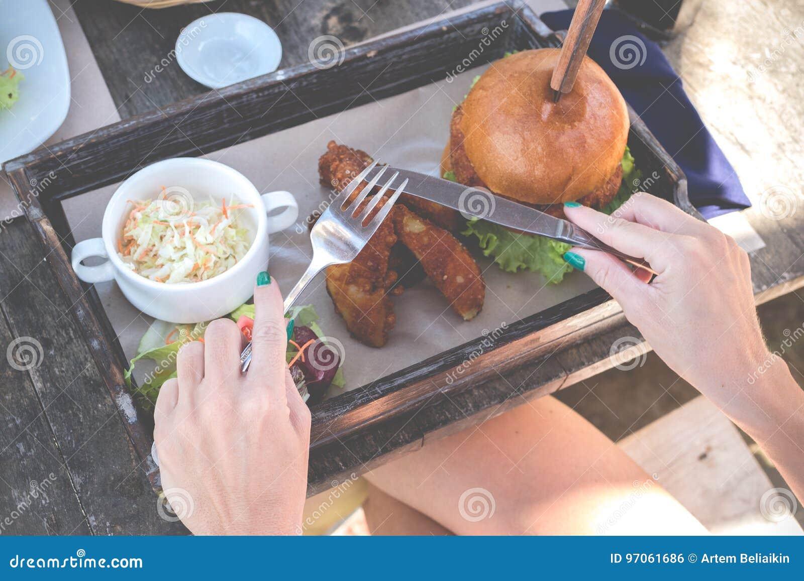 Zakończenie Up kobiet ręki Trzyma rozwidlenie i nóż na Wyśmienicie hamburgerze Amerykański fast food w włoskiej restauraci na Bal