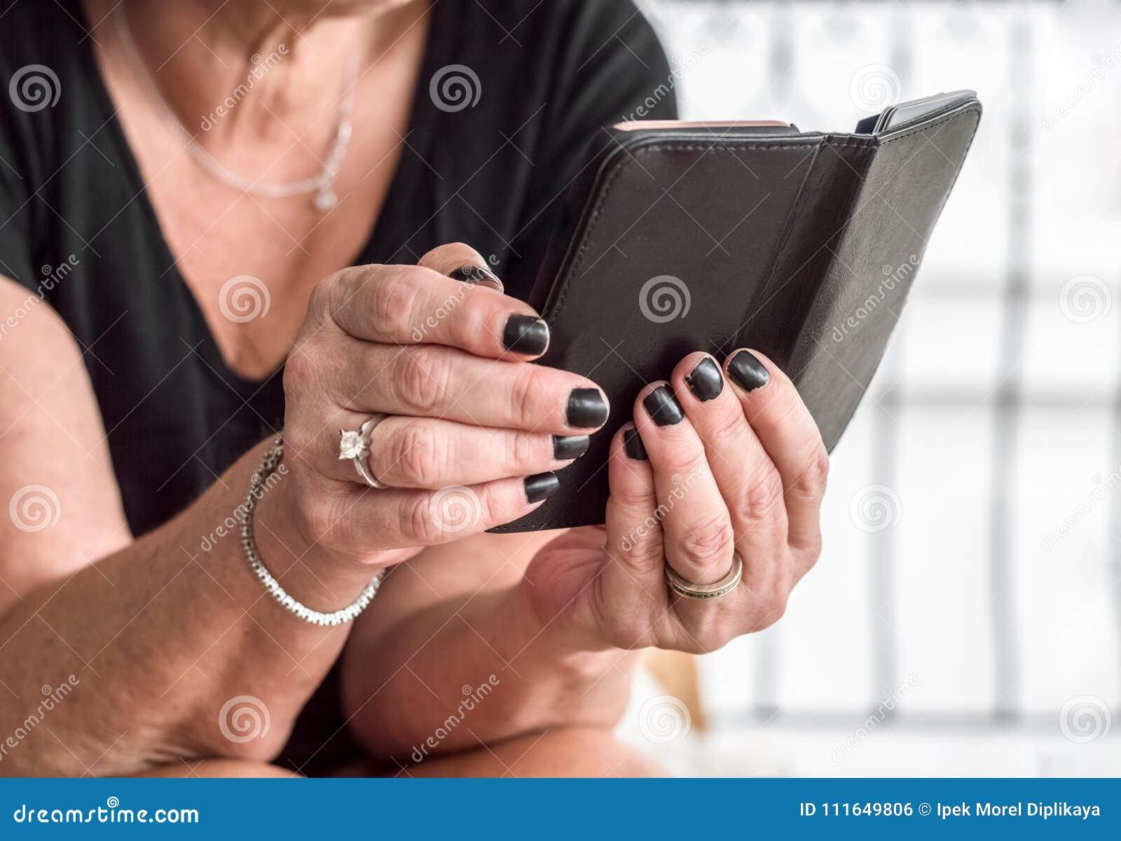 Zakończenie up kobiety stare ręki z czarnym gwoździa połysku mienia smartphone