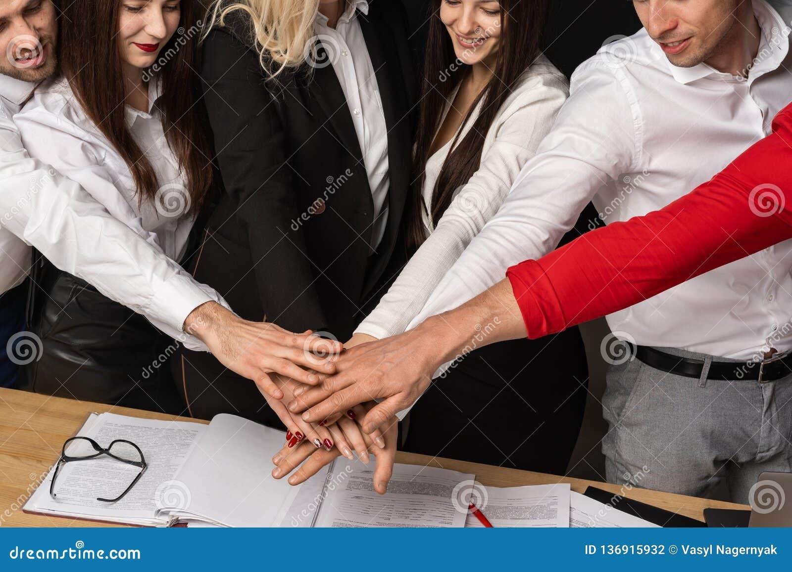 Zakończenie w górę cropped portreta pozytywni biznesmeni stawia ręki wpólnie