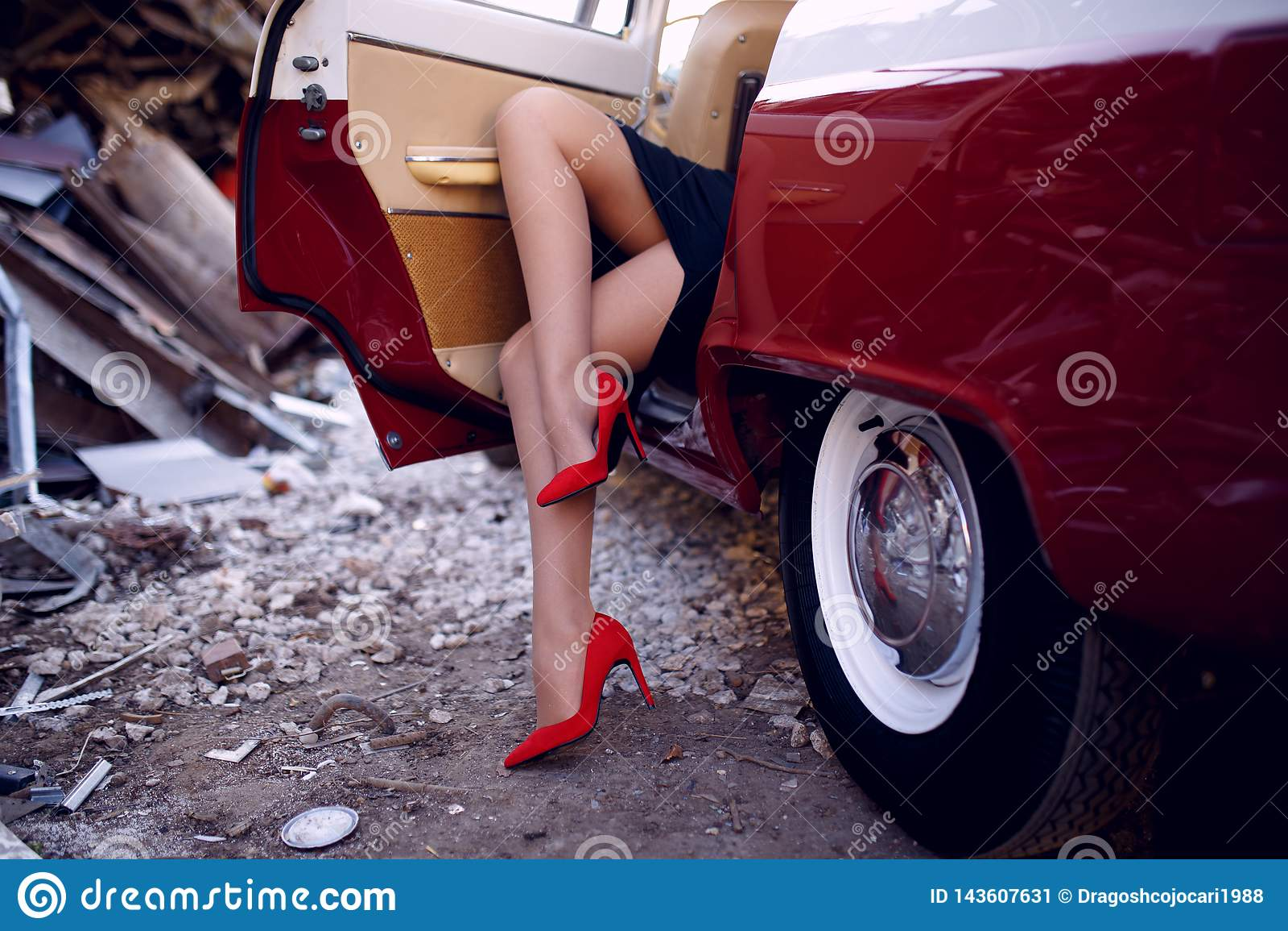 Zakończenie w górę kobiety siedzi wśrodku rocznika czerwonego samochodu na żelaznym usypu tle na iść na piechotę w czerwonych but