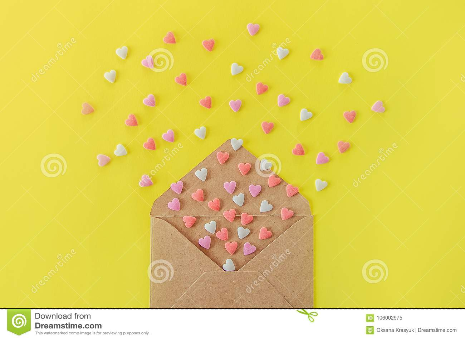 Zakończenie w górę Multicolor cukierki cukrowego cukierku serc lata z rzemiosło papieru koperty na jaskrawym żółtym tle pary dzie