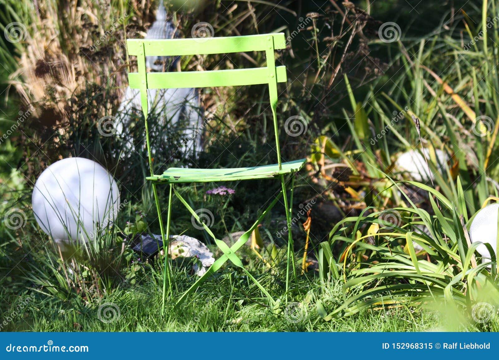 Zakończenie w górę osamotnionego odosobnionego zielonego drewnianego falcowania krzesła w ogródzie z trawami, zielona płocha, ele