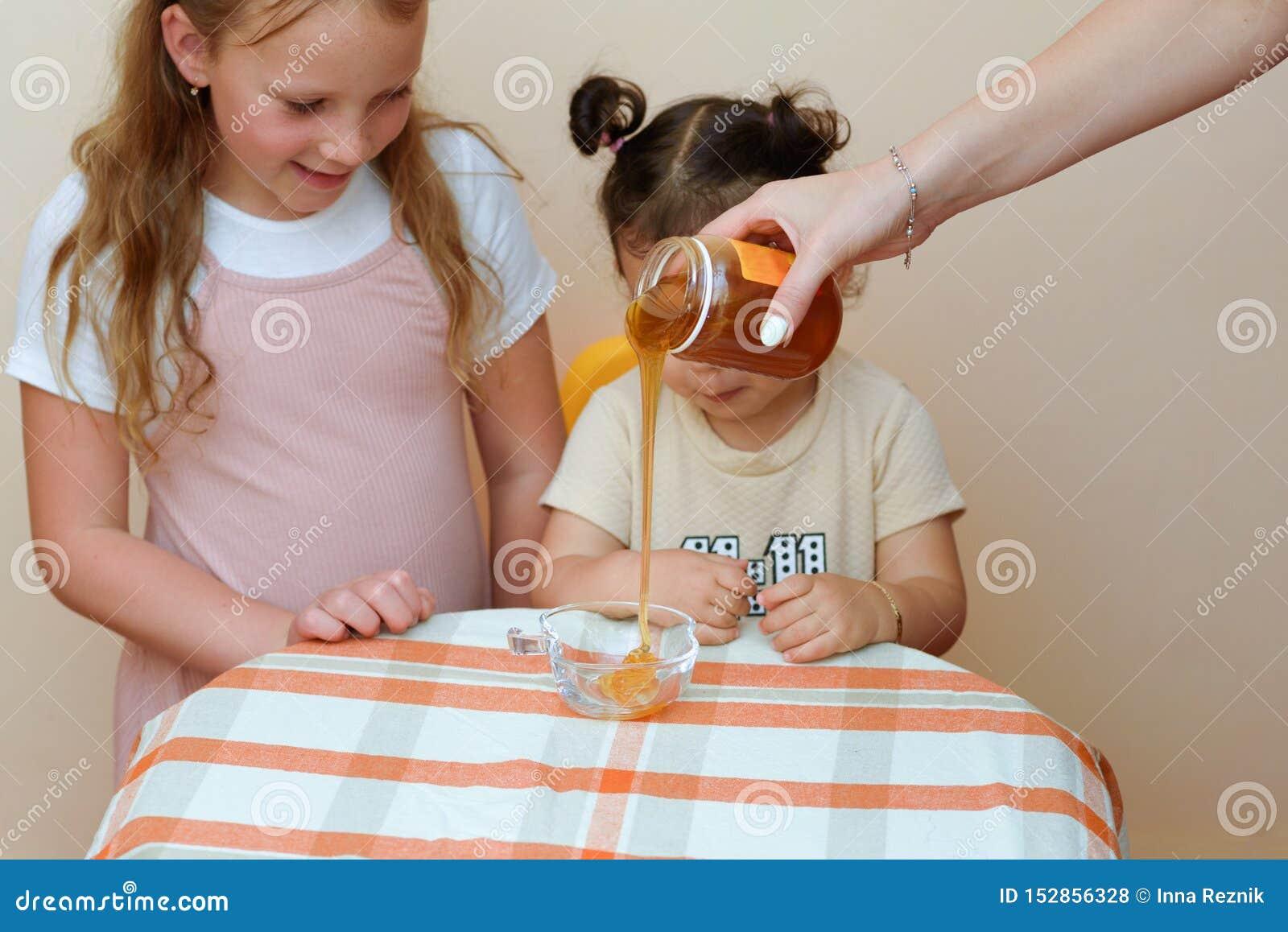 Zakończenie w górę portreta dwa śmieszna śliczna mała dziewczynka patrzeje na kobiety ręce nalewa świeżego miód od słoju w puchar