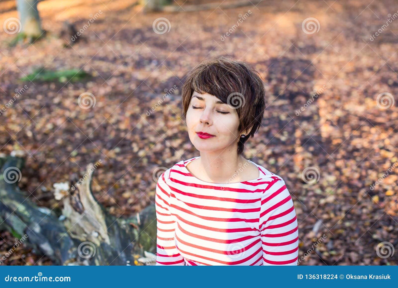 Zakończenie w górę portreta młoda uśmiechnięta kobieta siedzi i relaksuje na spadać drzewie w jesiennej lasowej jesieni z zamknię