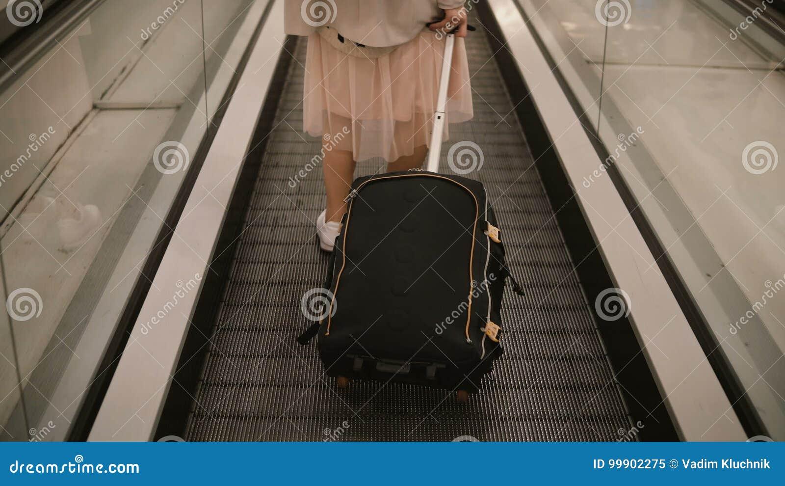 Zakończenie widok młoda kobieta z walizki pozycją na eskalatorze w lotnisku Modnisia żeński przygotowywający iść ono potykać się