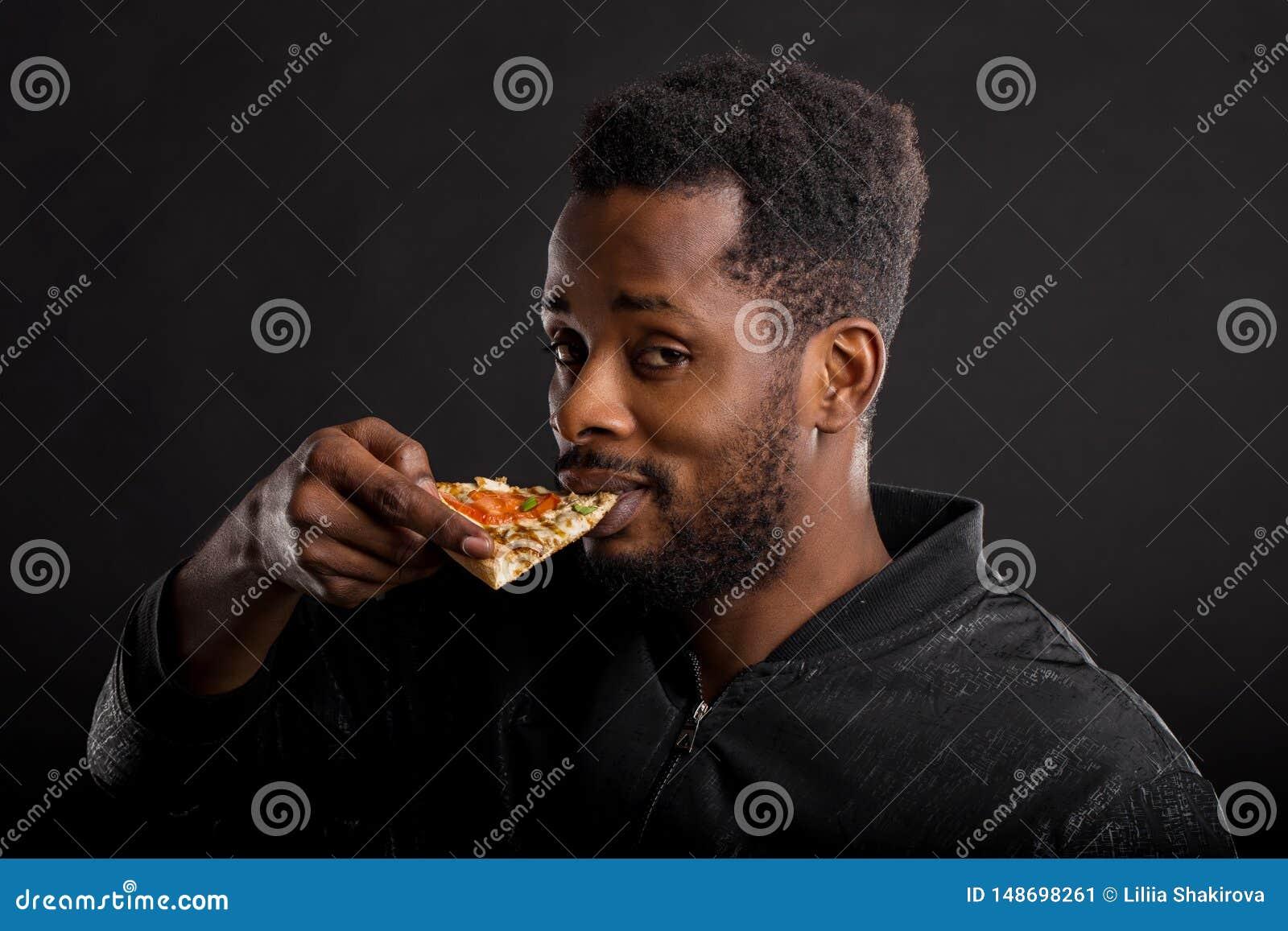 Zako?czenie w g?r? portreta m?oda afryka?ska m??czyzny ?asowania pizza