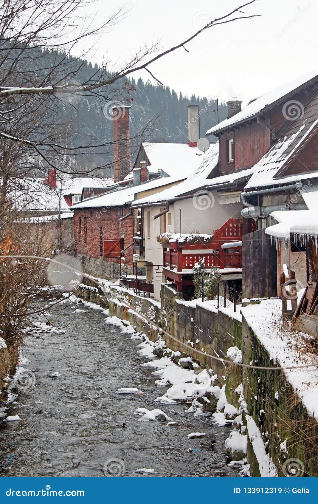 Zakopane-Stadt während des Schneiens, der Bäume, der Zäune und der alten Häuser entlang dem Gebirgsstrom