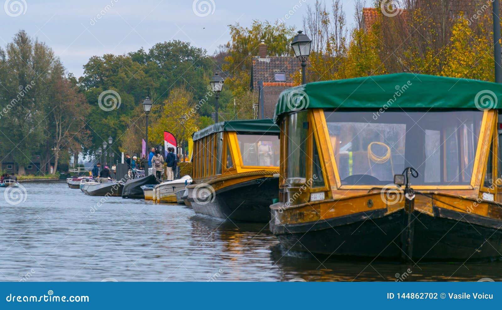 Zakrywać łodzie na wodnych kanałach w Giethoorn holandiach i drzewach na spadku dniu,