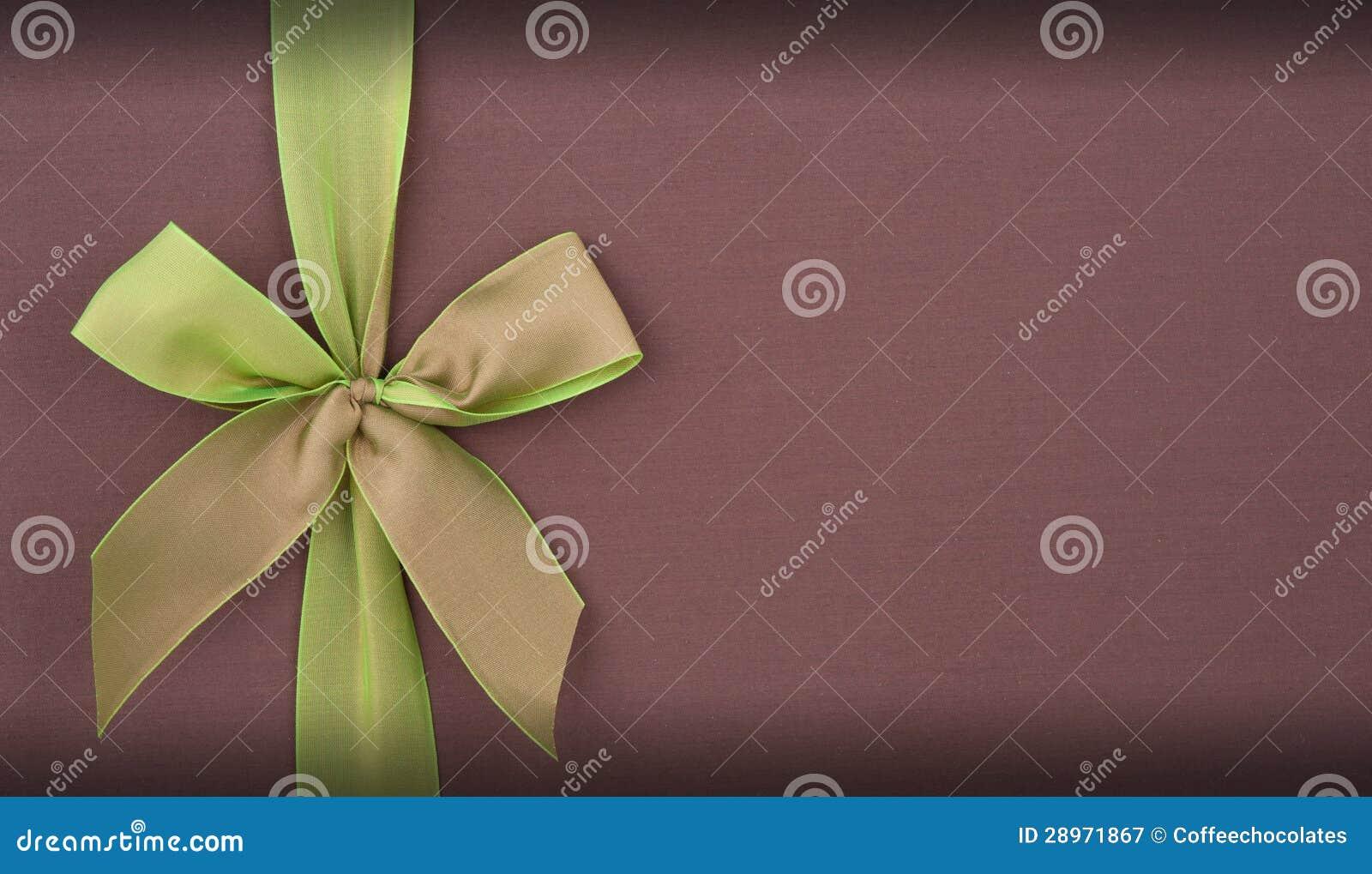 Zakrywa prezenta pudełko z zielonym łękiem