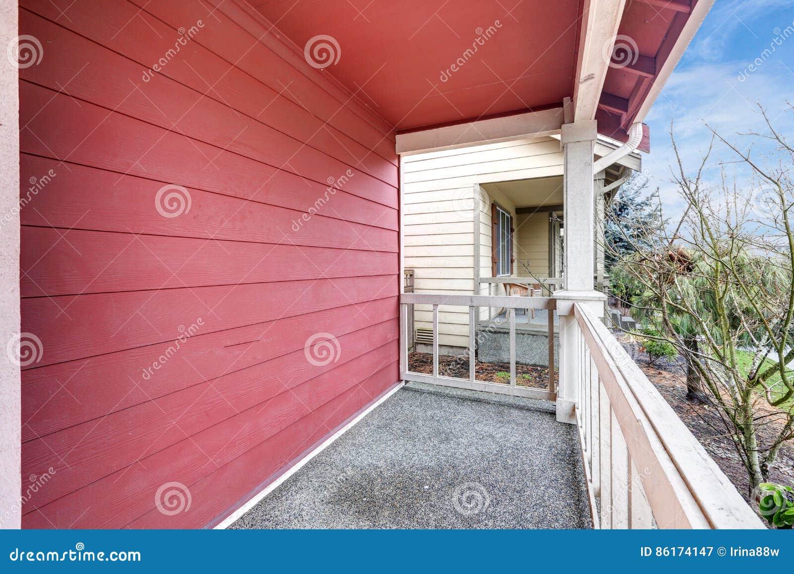 Zakrywający czerwony ganek frontowy z poręczami