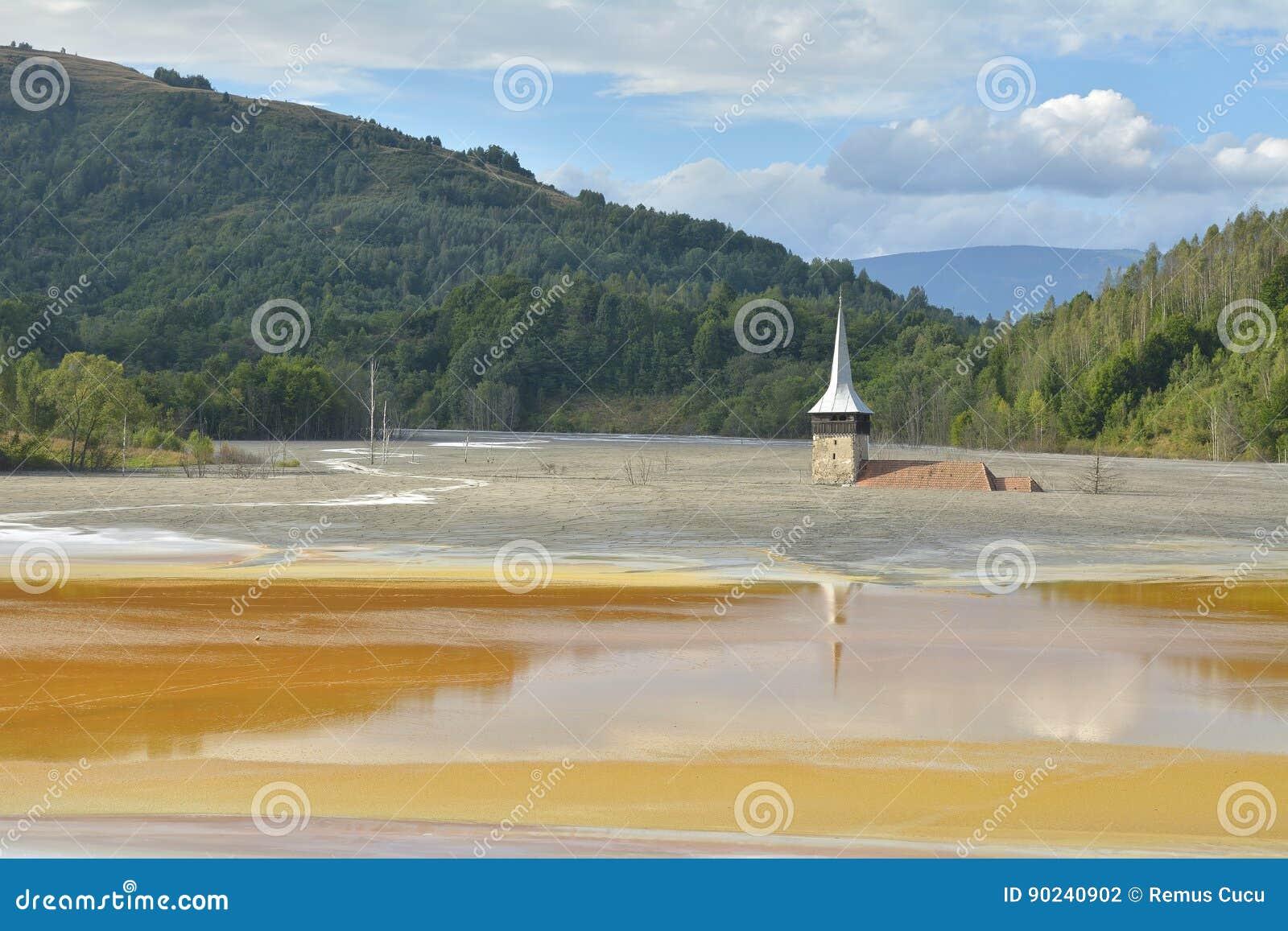 Zalewający i zaniechany kościół po środku skażonego jeziora