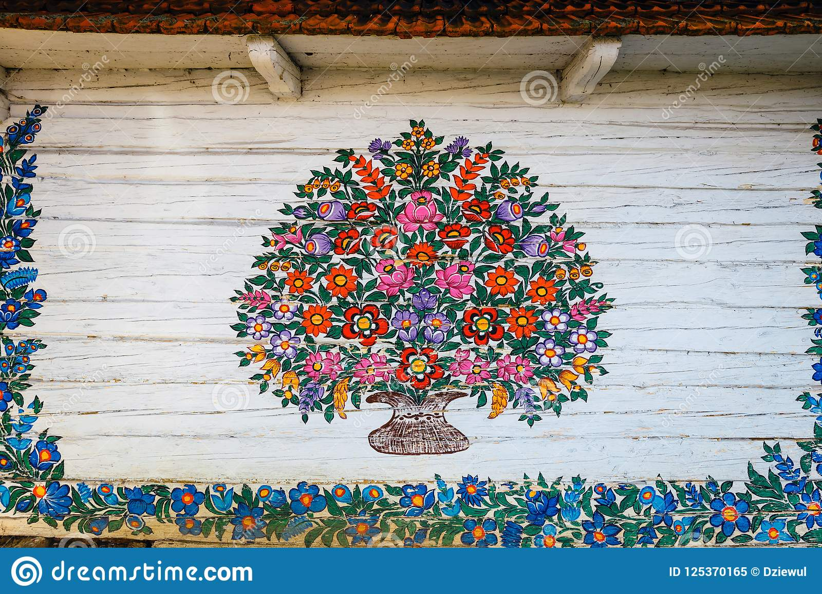 Zalipie, Poland, August 19, 2018: Close up of colorful flowers painted on wooden cottage in Zalipie, Poland. It is known for a lo