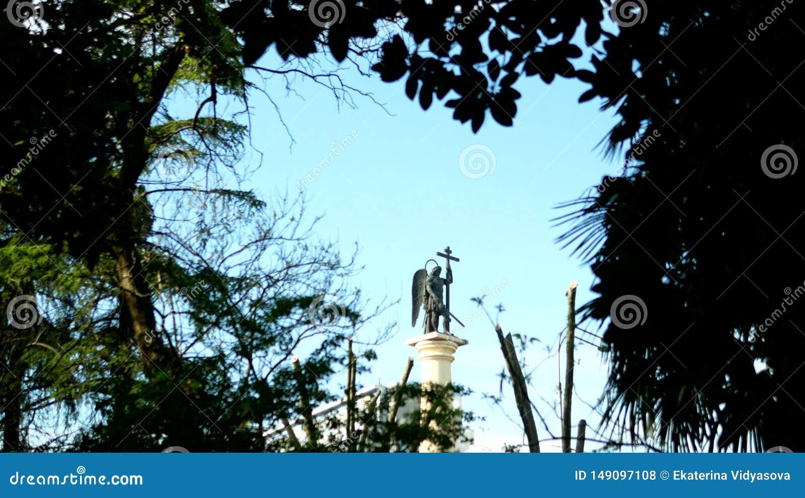 Zamazana sylwetki statua anio? z kordzikiem przeciw niebieskiemu niebu w ramie ulistnienie