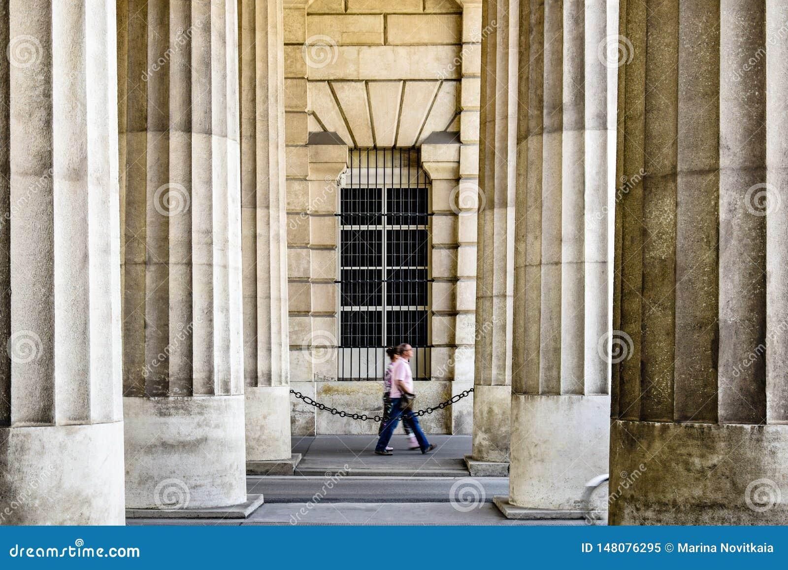 Zamazane sylwetki turyści chodzi wśród ogromnych majestatycznych kolumn stary budynek