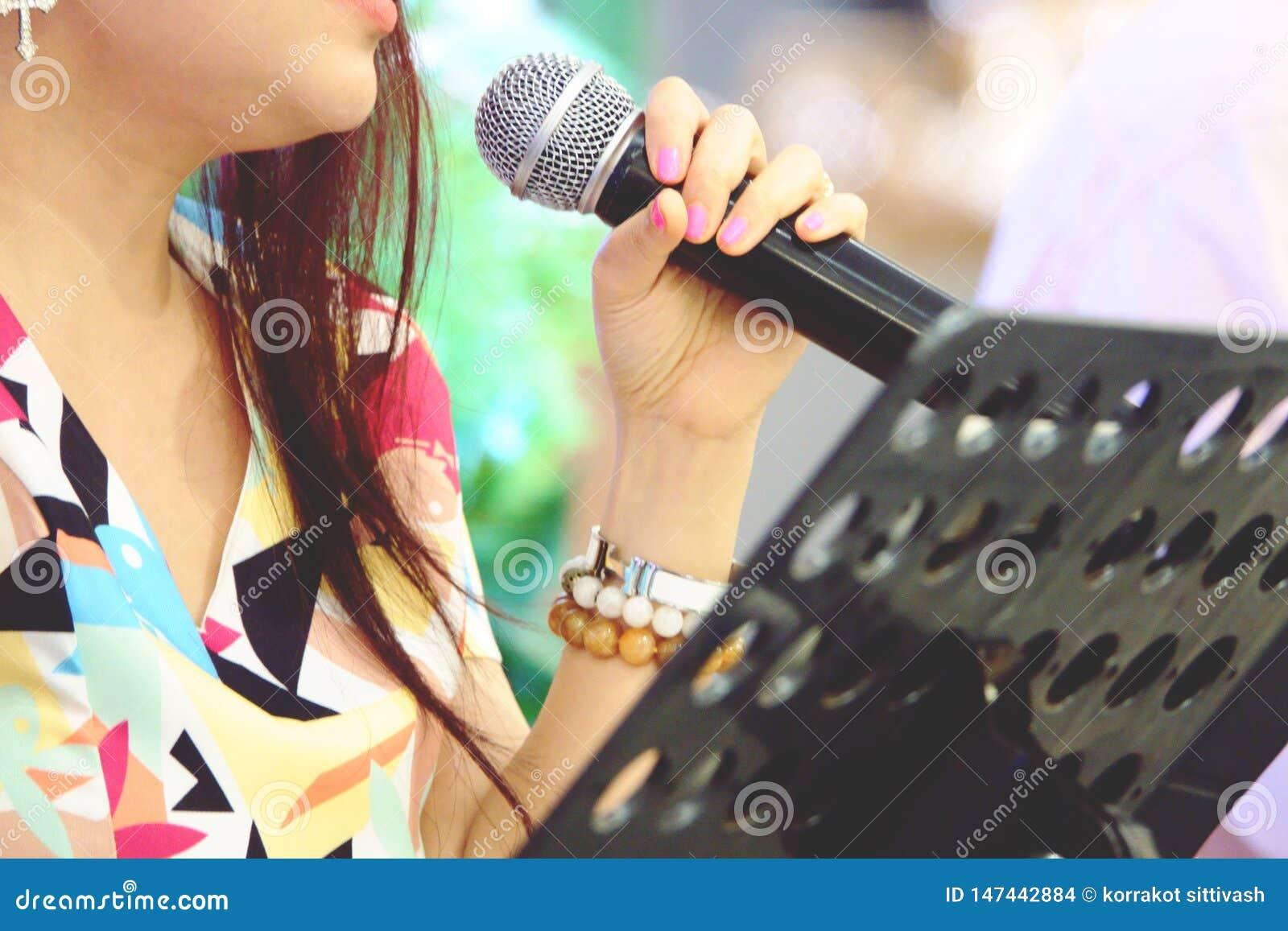 Zamazany Asia piosenkarz wr?cza mienie mikrofon na scenie