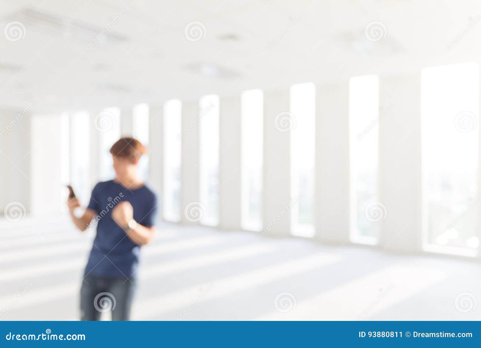 Zamazany obrazek Szczęśliwy młodego człowieka mienia smartphone i celebra