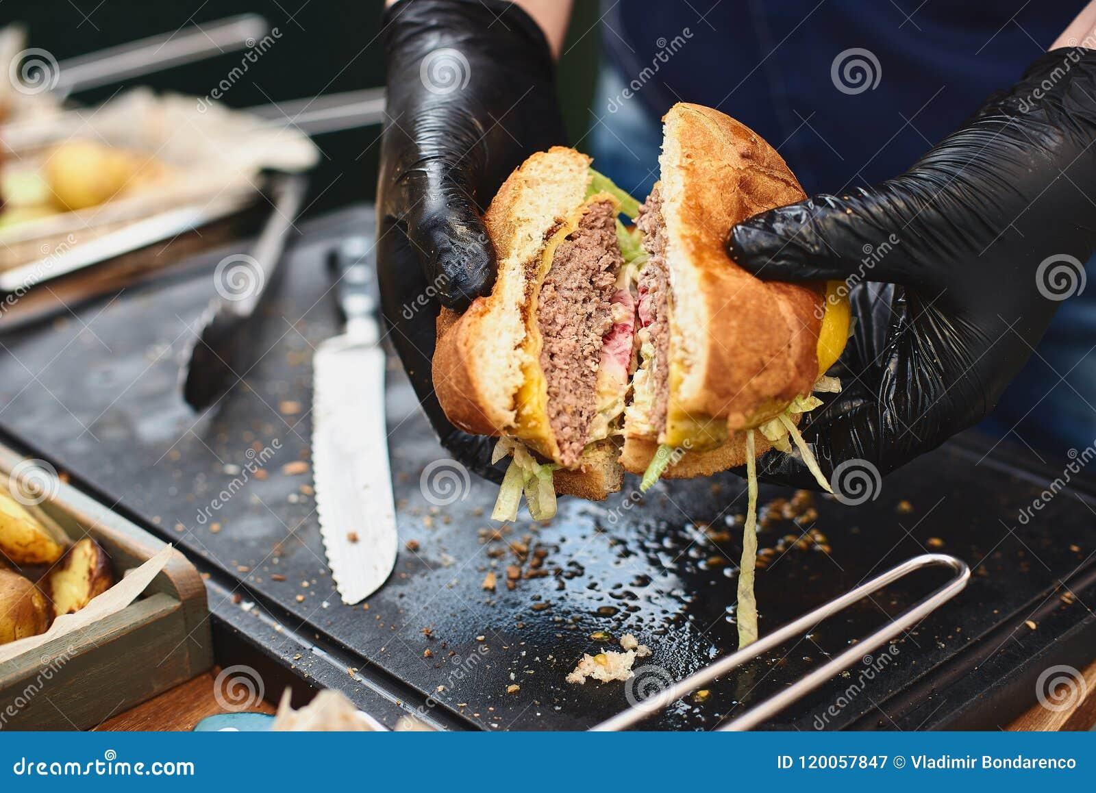 Zamyka up appetising wołowina hamburger Szefa kuchni ` s ręki dzielą w połówka gotujących hamburgery od wołowiny Uliczny karmowy