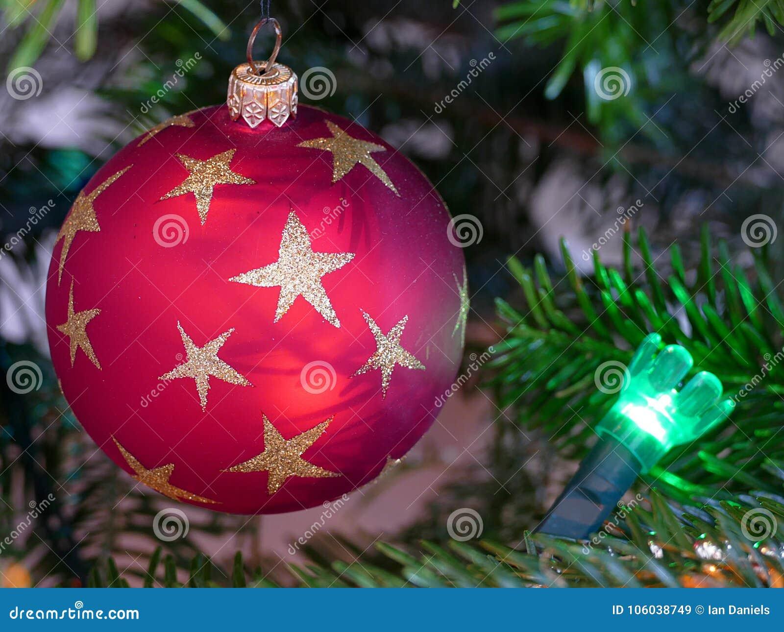 Zamyka up kółkowy czerwony bauble na choince z zielonym czarodziejskim światłem