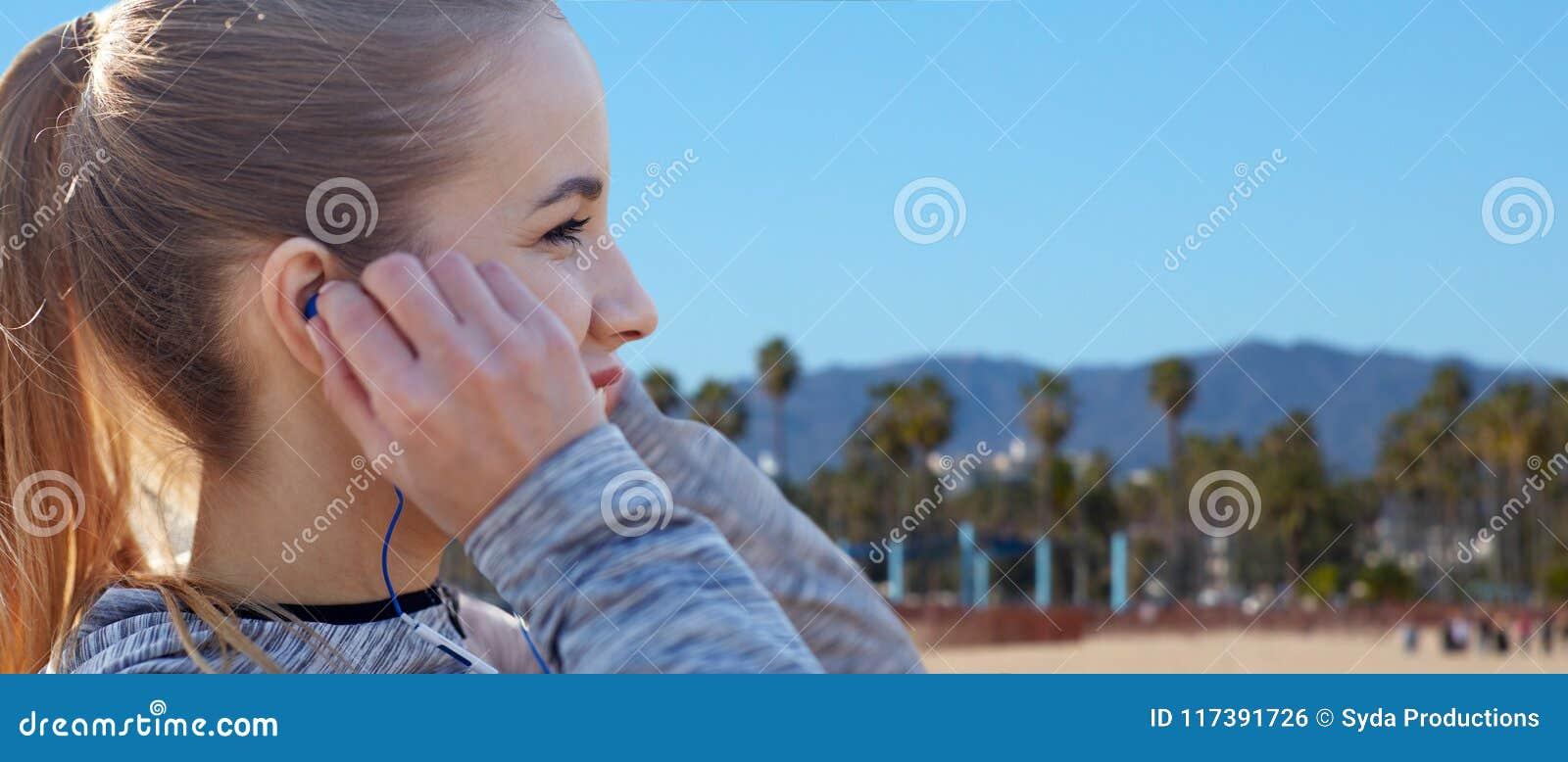 Zamyka up kobieta słucha muzyka w słuchawkach