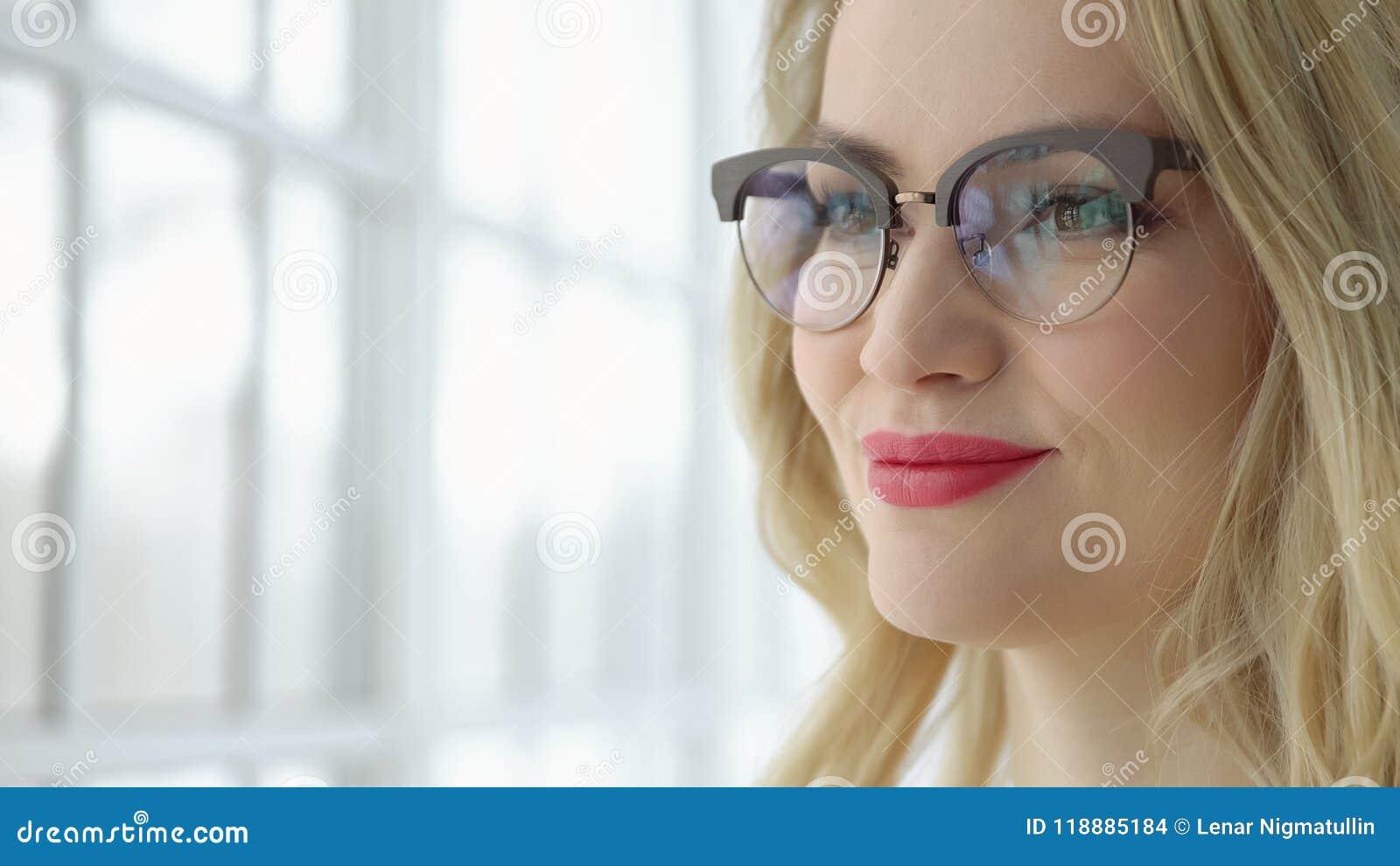 Zamyka up młoda kobieta w szkłach i czarnej sukni okno