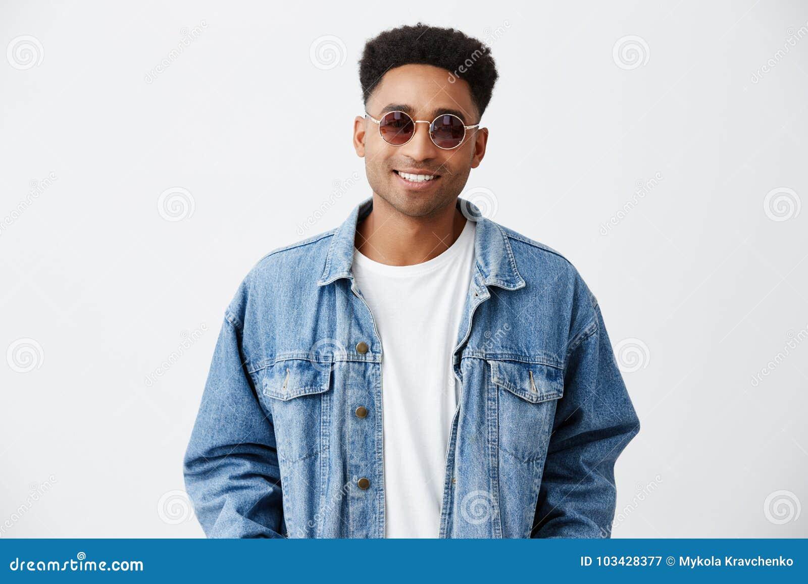 Zamyka up młody atrakcyjny rozochocony modny ciemnoskóry mężczyzna z afro fryzurą w białej koszula pod drelichem