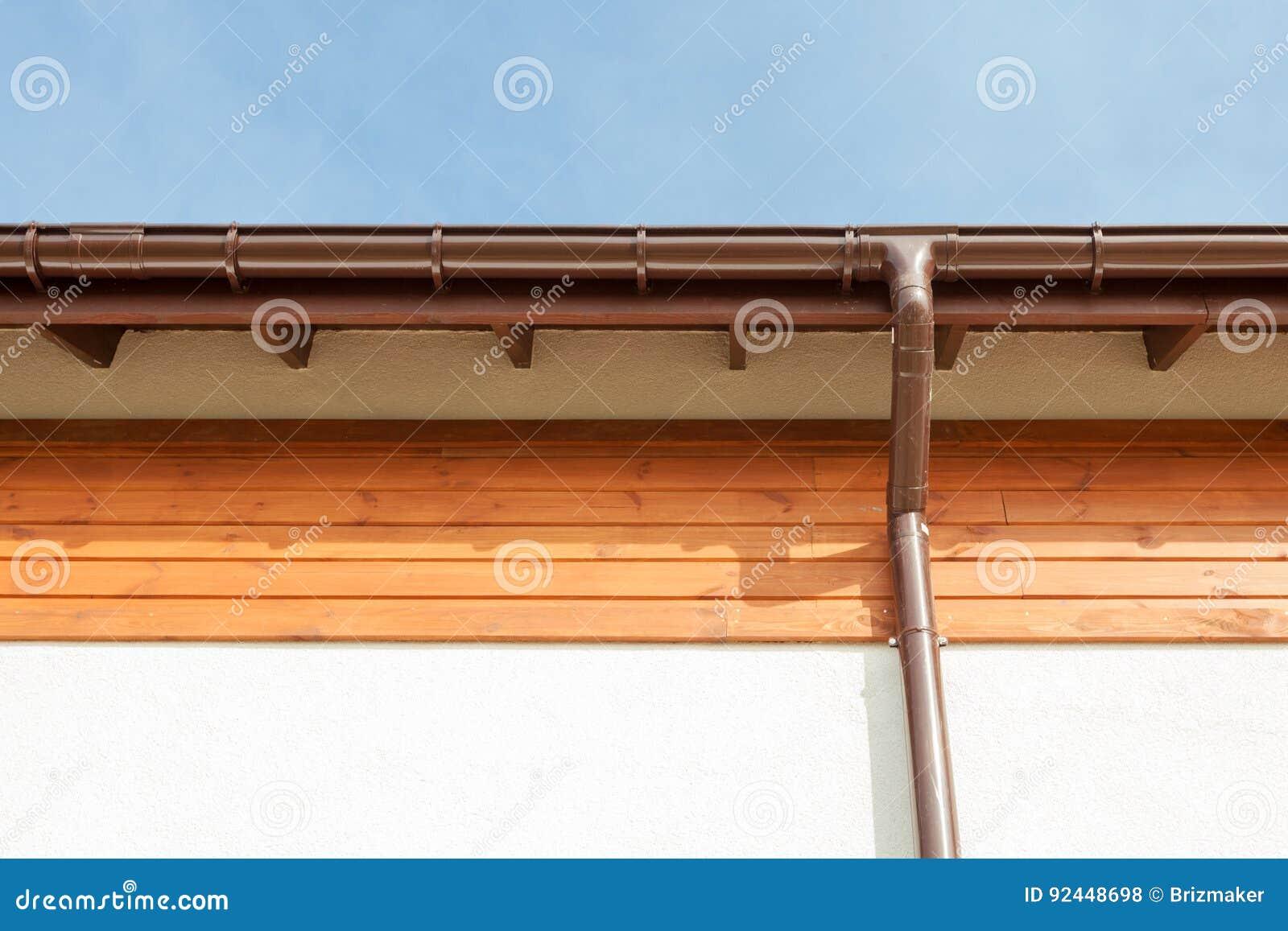 Zamyka up na Nowej Podeszczowej rynnie, Downspout, Soffit deska, Fascia Deskowa instalacja Przeciw niebieskiemu niebu