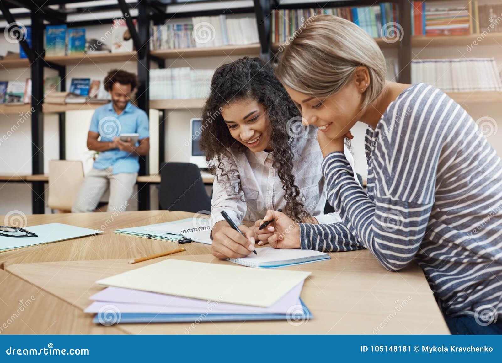 Zamyka up par piękne młode etniczne studenckie dziewczyny robi pracie domowej wpólnie, pisać eseju dla prezentaci