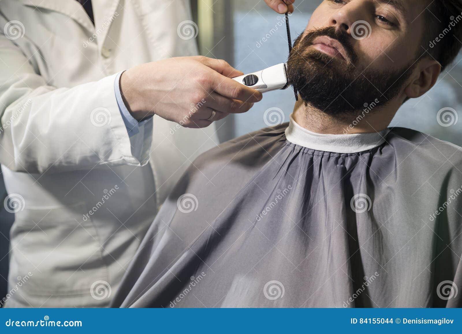 Zamyka up poważny brown z włosami biznesmen ma jego brodę czeszącą i żyłującą w fryzjera męskiego sklepie