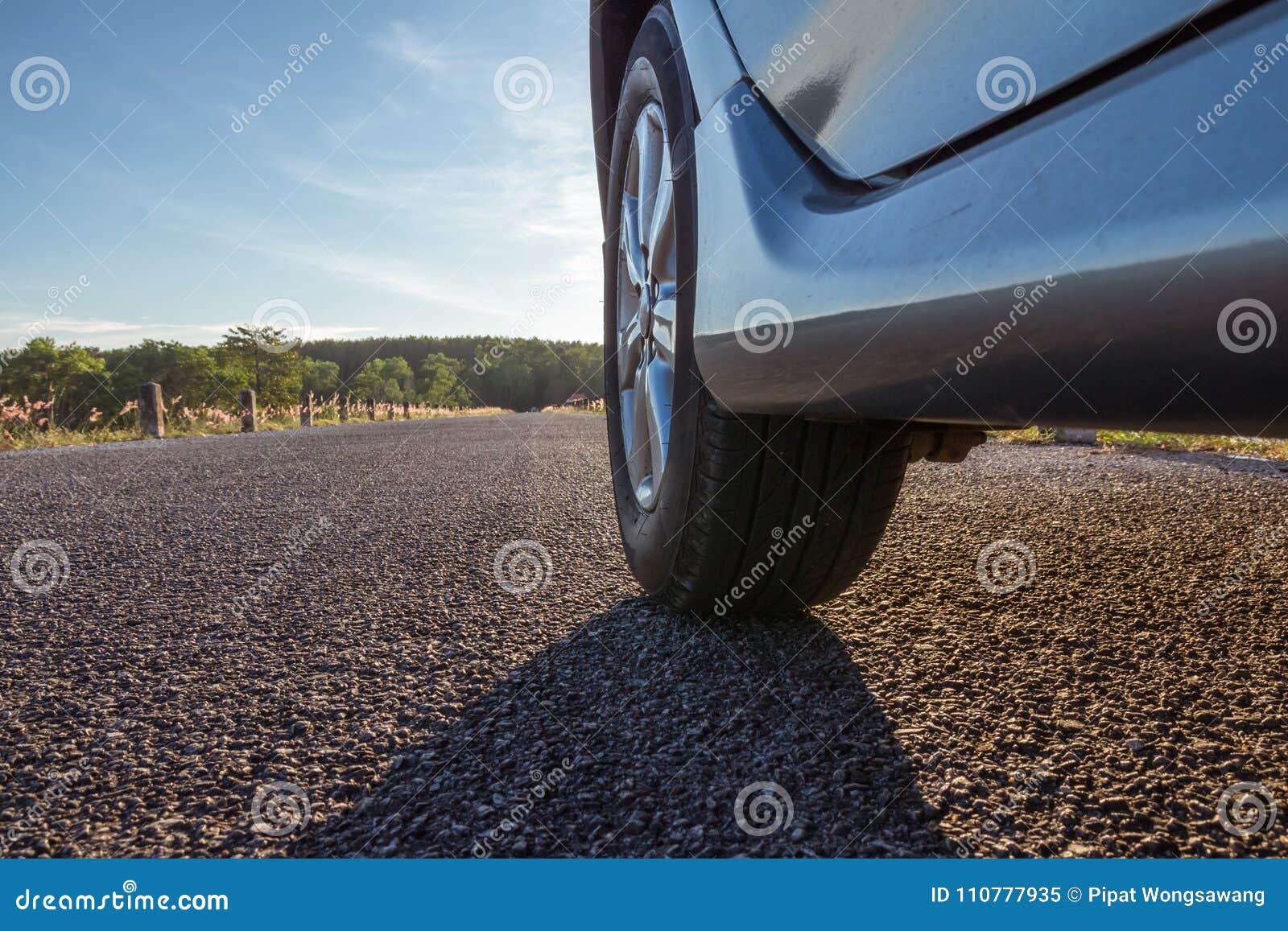 Zamyka up samochodowi koła na asfaltowej drodze