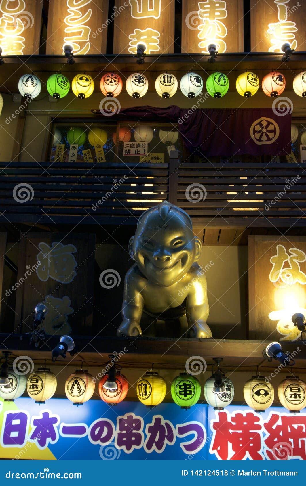 Zamyka w górę obrazka złota Billiken statua i billboardy Japońska restauracja w Osaka