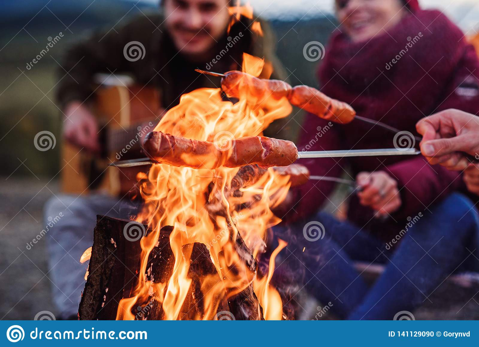 Zamyka w górę ogniska i firmy przyjaciele które wypiekowe kiełbasy tam Piją energetycznych napoje, śpiew i