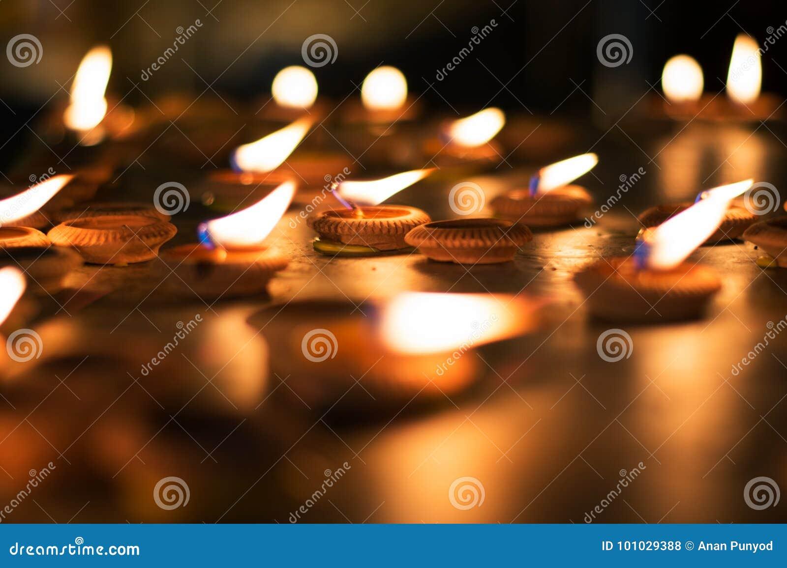 Zamyka w górę żarówek lub Zaświecającej świeczki uwielbiać Buddha w nighttime