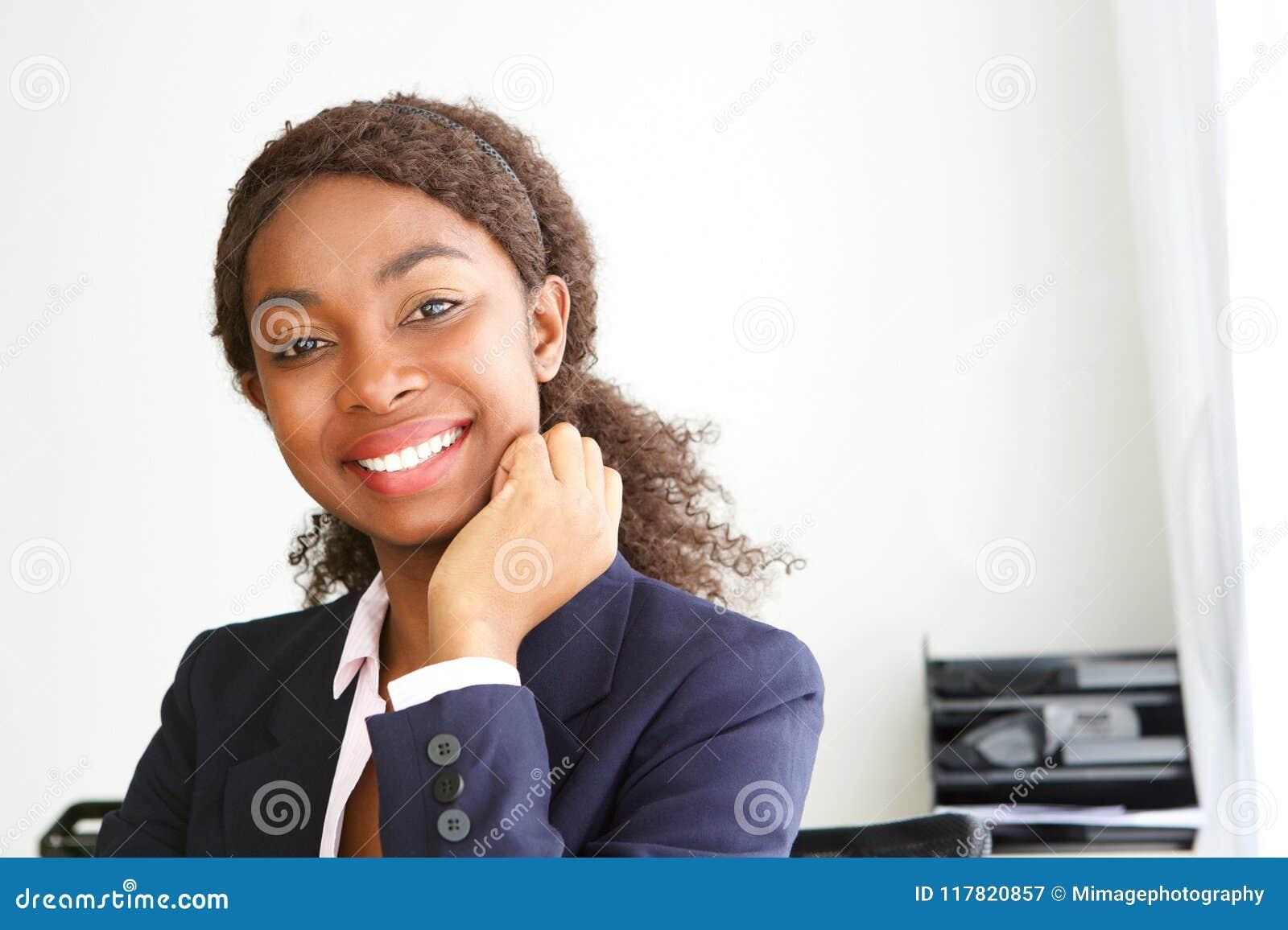 Zamyka w górę atrakcyjnego młodego afrykańskiego bizneswomanu ono uśmiecha się w biurze