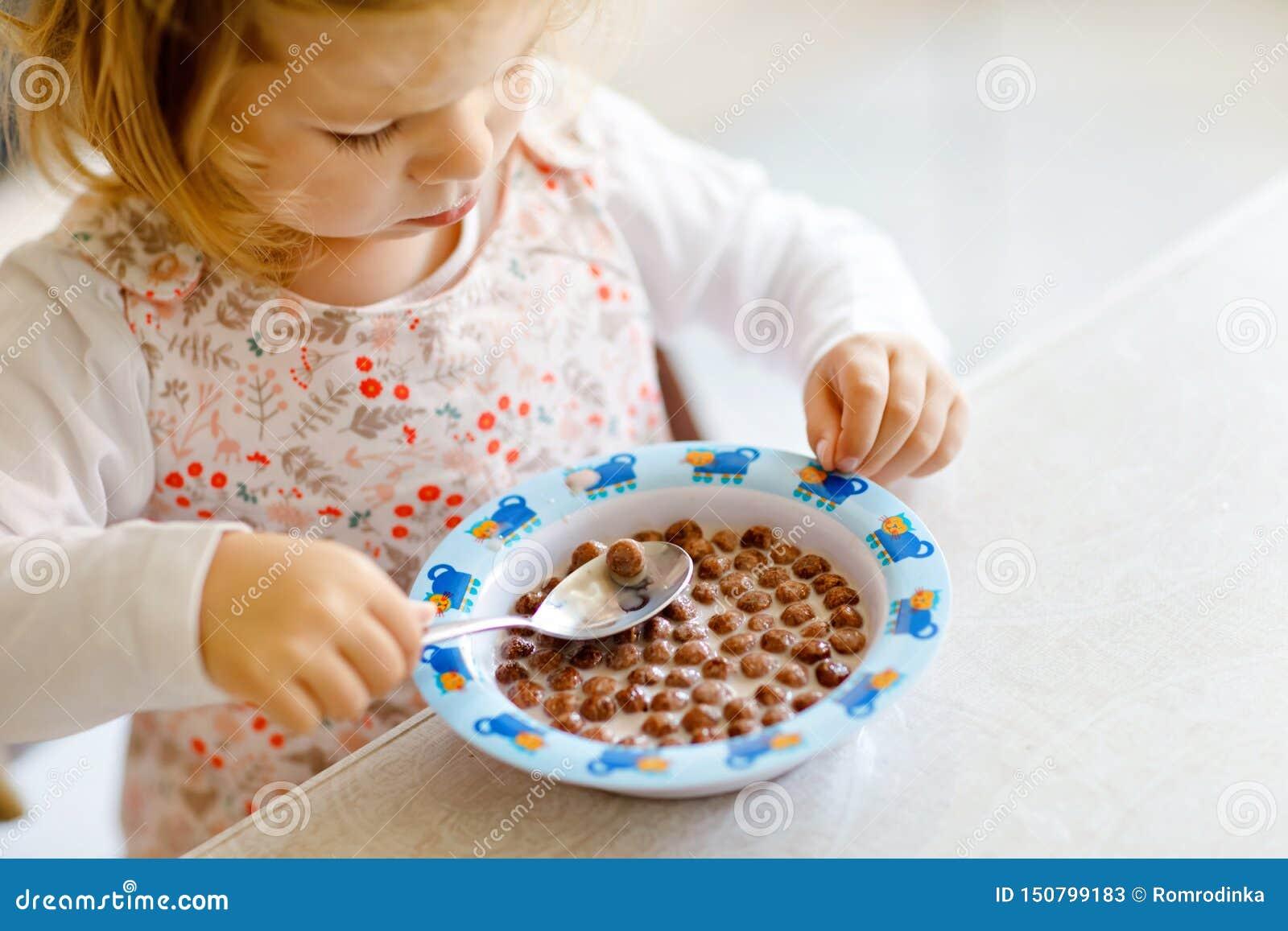 Zamyka w górę berbeć dziewczyny je zdrowego zboża z mlekiem dla śniadaniowego Ślicznego szczęśliwego dziecka dziecka w kolorowych