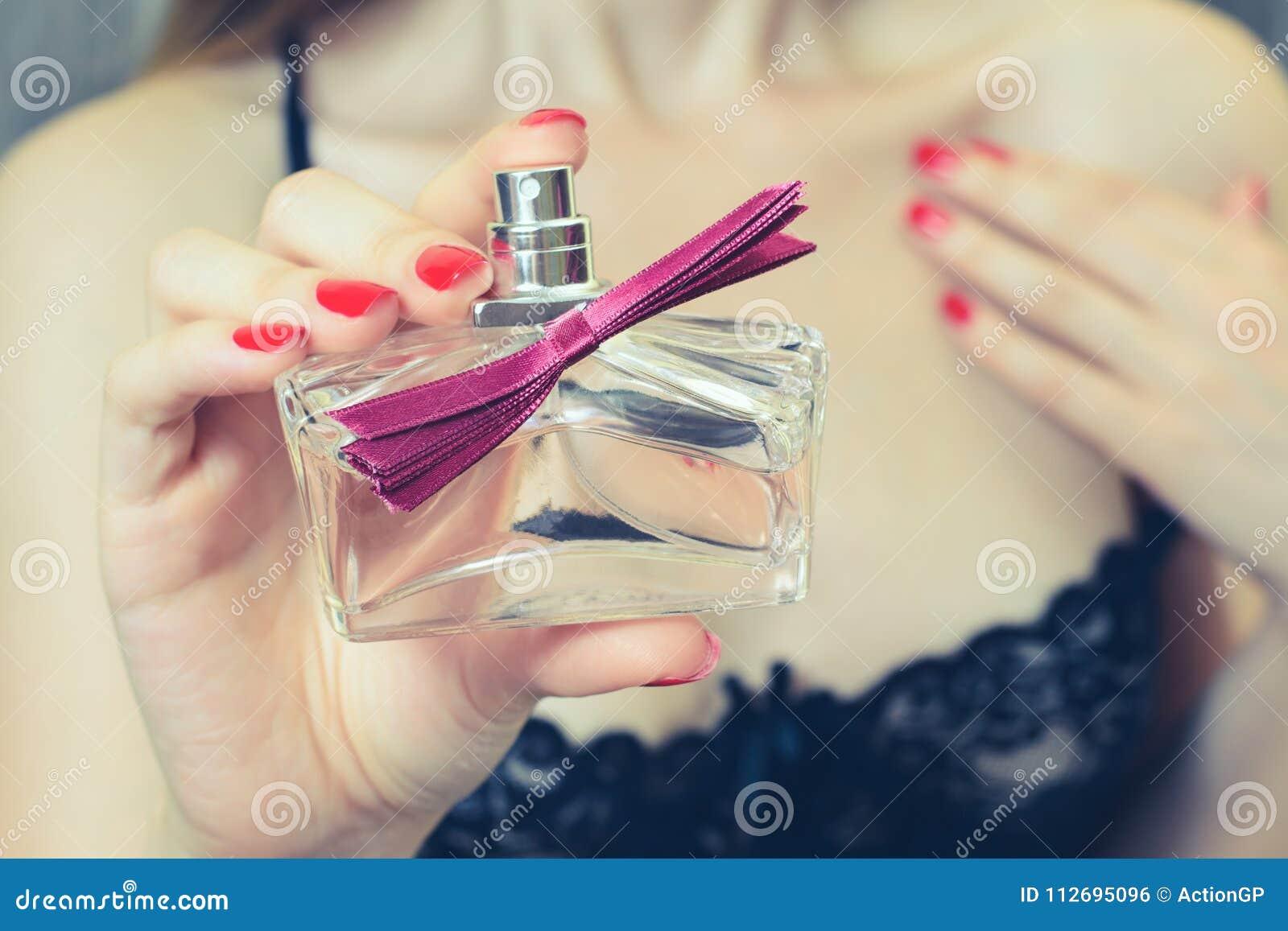 Zamyka w górę cropped widok fotografii Kobieta w uwodzicielskim odziewa pokazywać butelkę pachnidło, uwodzicielski piękny atrakcy