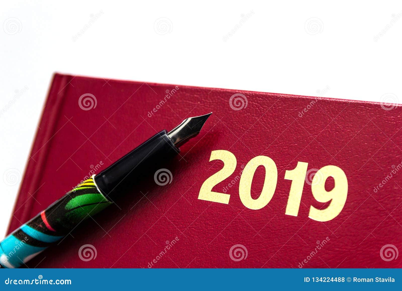 Zamyka w górę 2019 czerwonych rzemiennych dzienniczków z fontanny piórem na białym tle